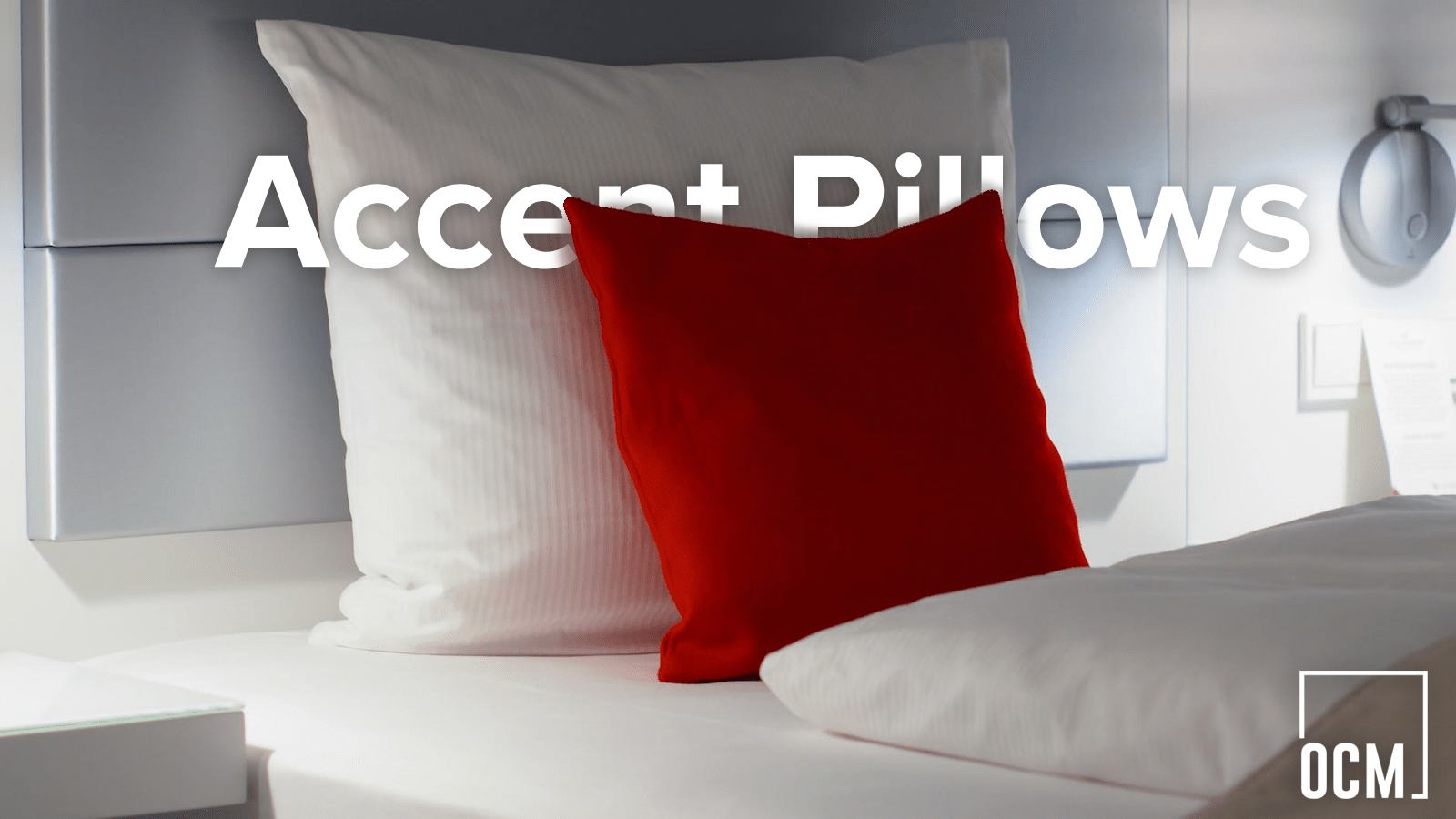 red pillow and white pillow on a bed