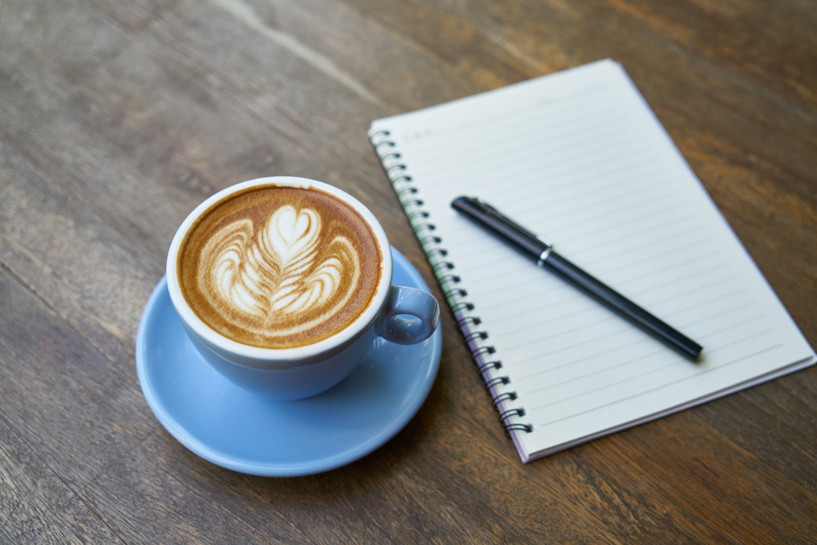 A latte sits next to a journal perfect for schoolwork or studying.