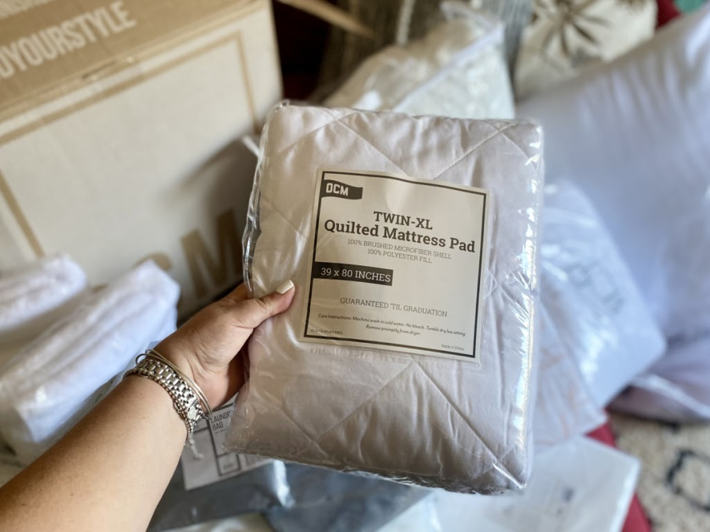 Person holding OCM Twin XL Mattress Pad in package