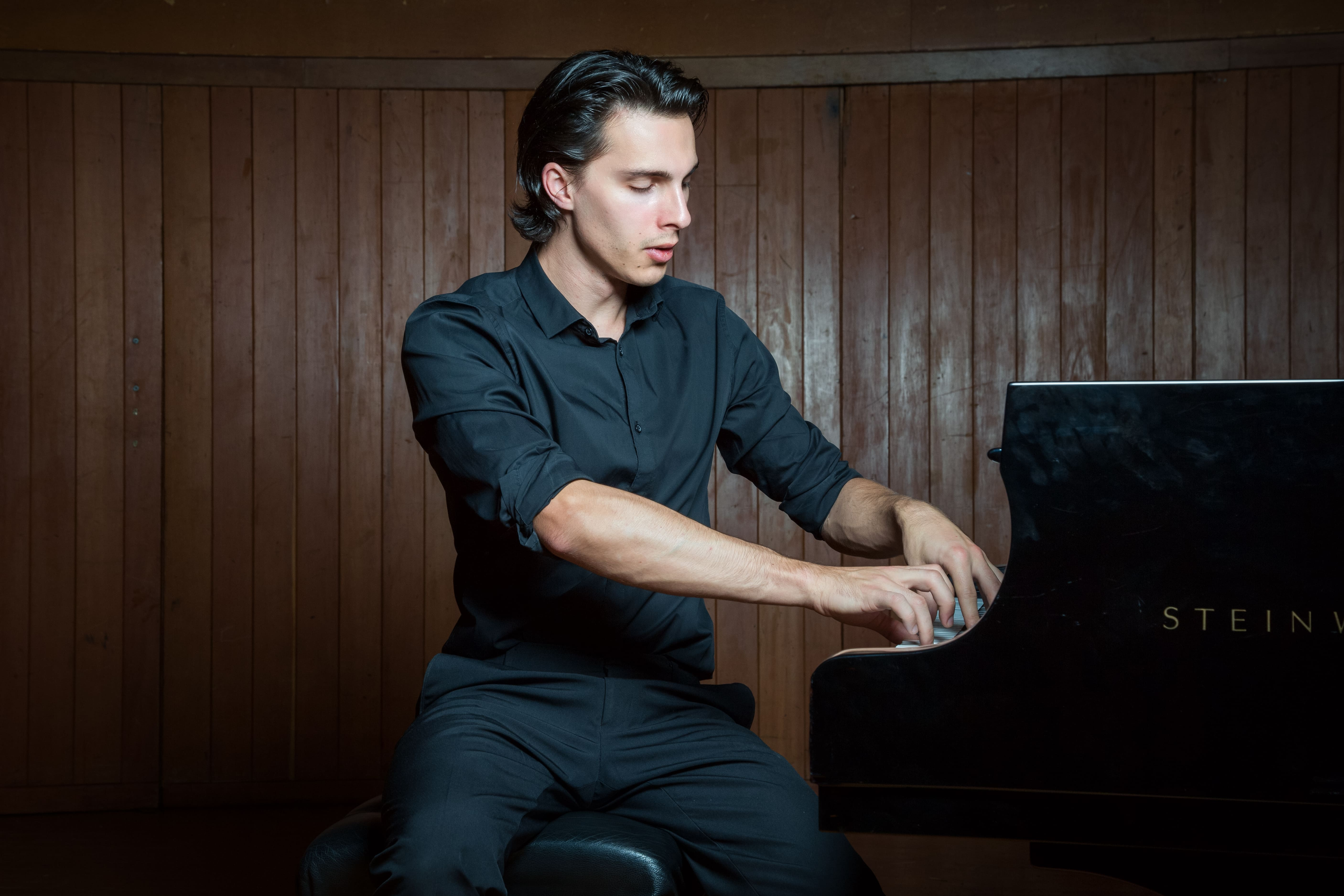 Composer & pianist from South Africa Liam Pitcher sitting at a Steinway & Sons grand piano at the Baxter Theater.