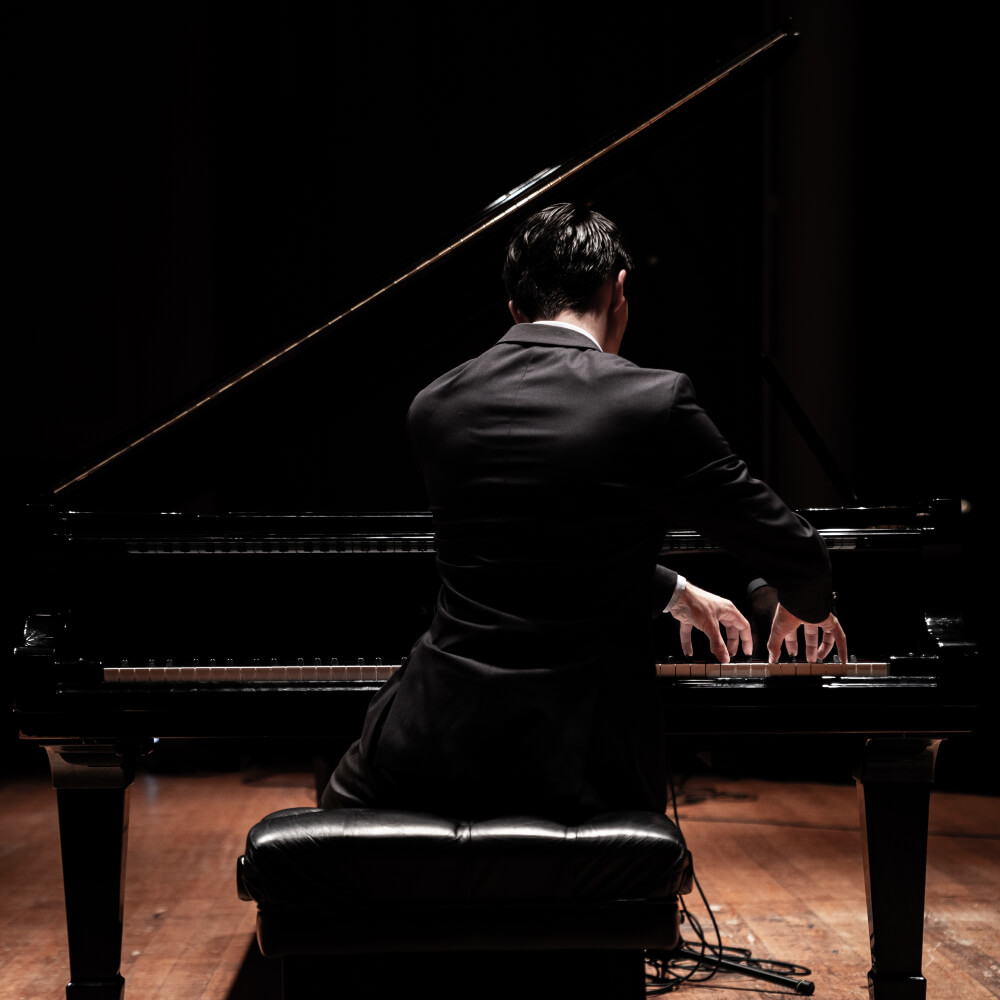 A photo of the famous classical composer and pianist 'Liam Pitcher' playing a Steinway and Sons Grand Piano, shot from behind.