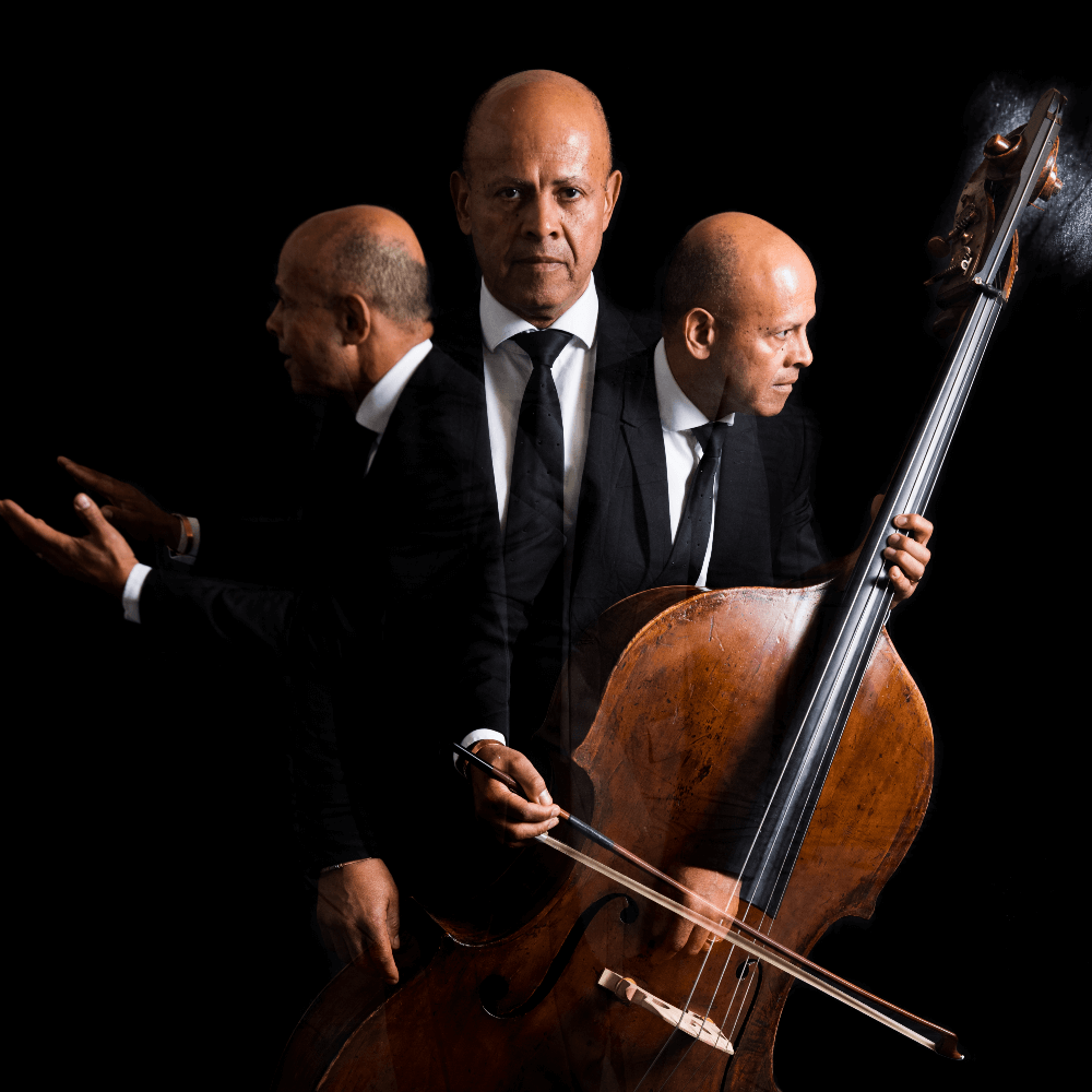 Leon Bosch and two mirror images of himself playing a double bass in the dark.