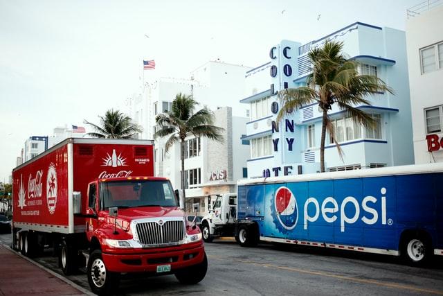Pepsi and Coke trucks at same location