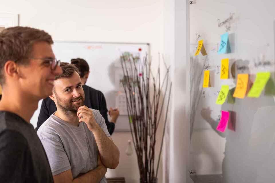 Florian und Philipp bei einem Workshop vor einer Tafel mit post-its