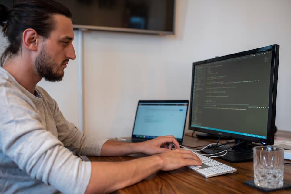 Oliver arbeitet an seinem Schreibtisch und programmiert