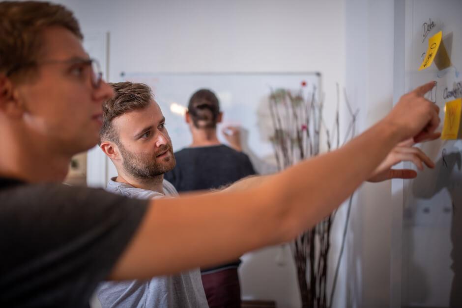 Philipp und Florian Zeigen auf Post-Its bei einem Workshop
