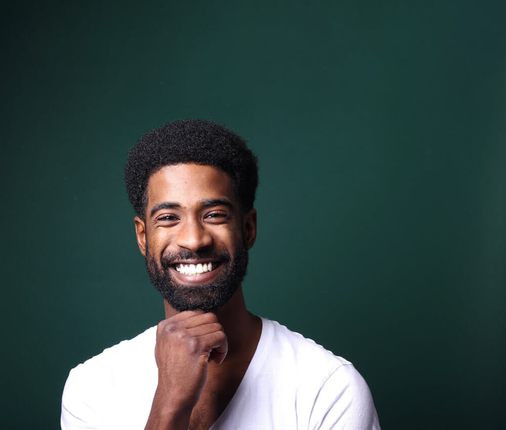 Platineers Smile. Young man smiling on green background.