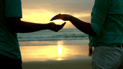 couple silhouette with hands encircling a sun setting on the beach