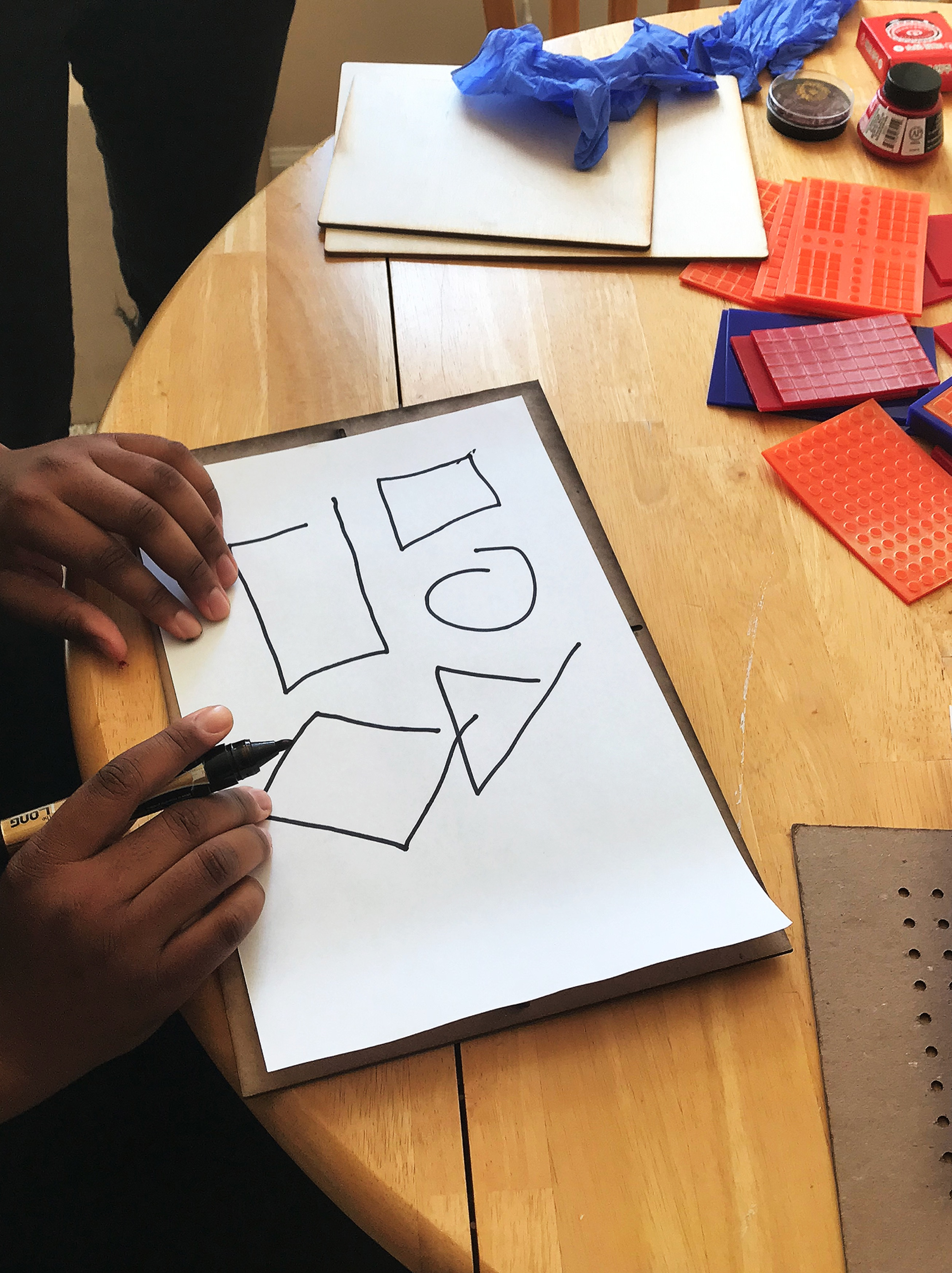 Contextual Inquiry mage showing a visually impaired participant drawing with a pen.