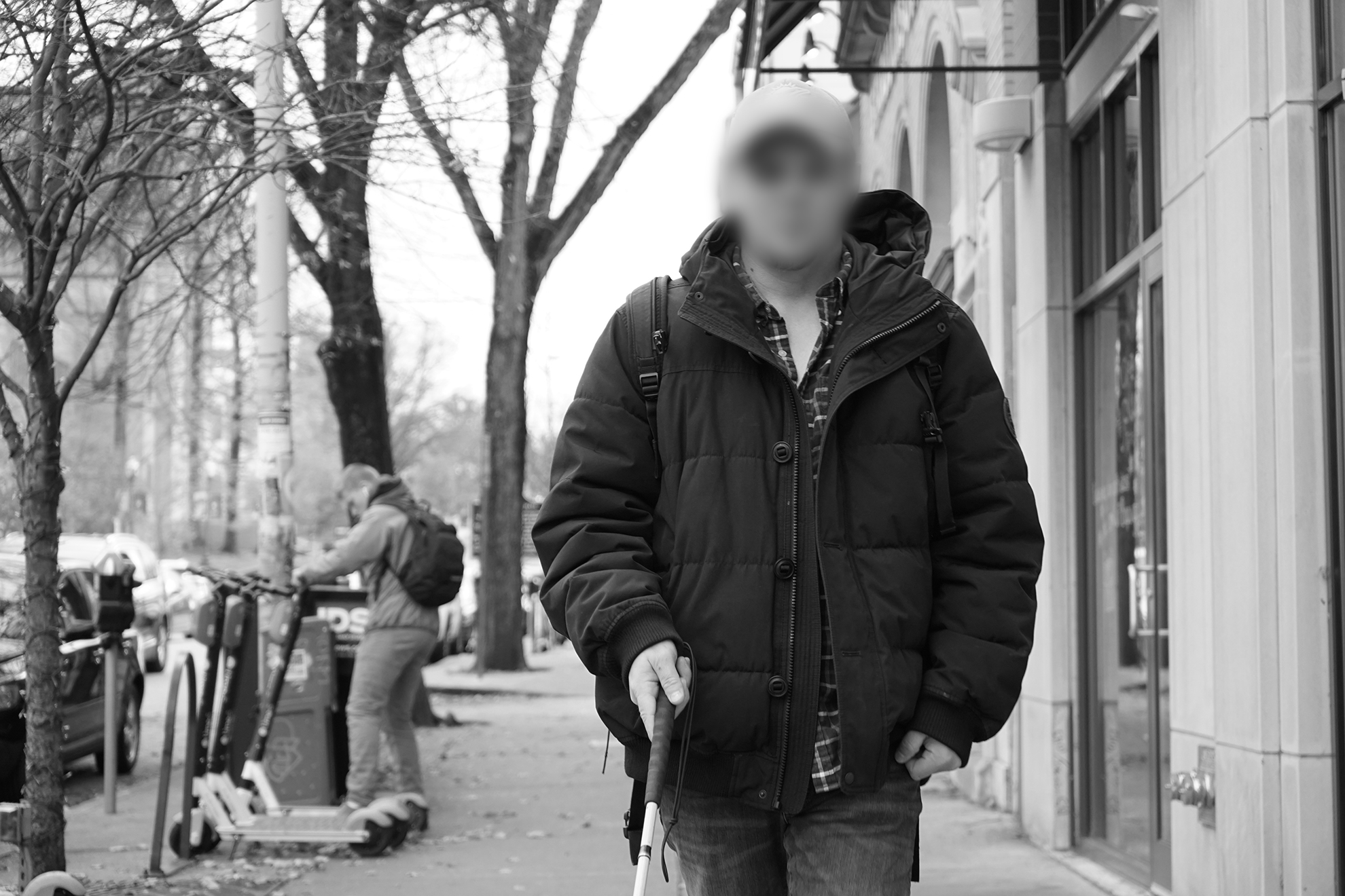 Image of a visually impaired participant walking on a sidewalk with a walking stick.