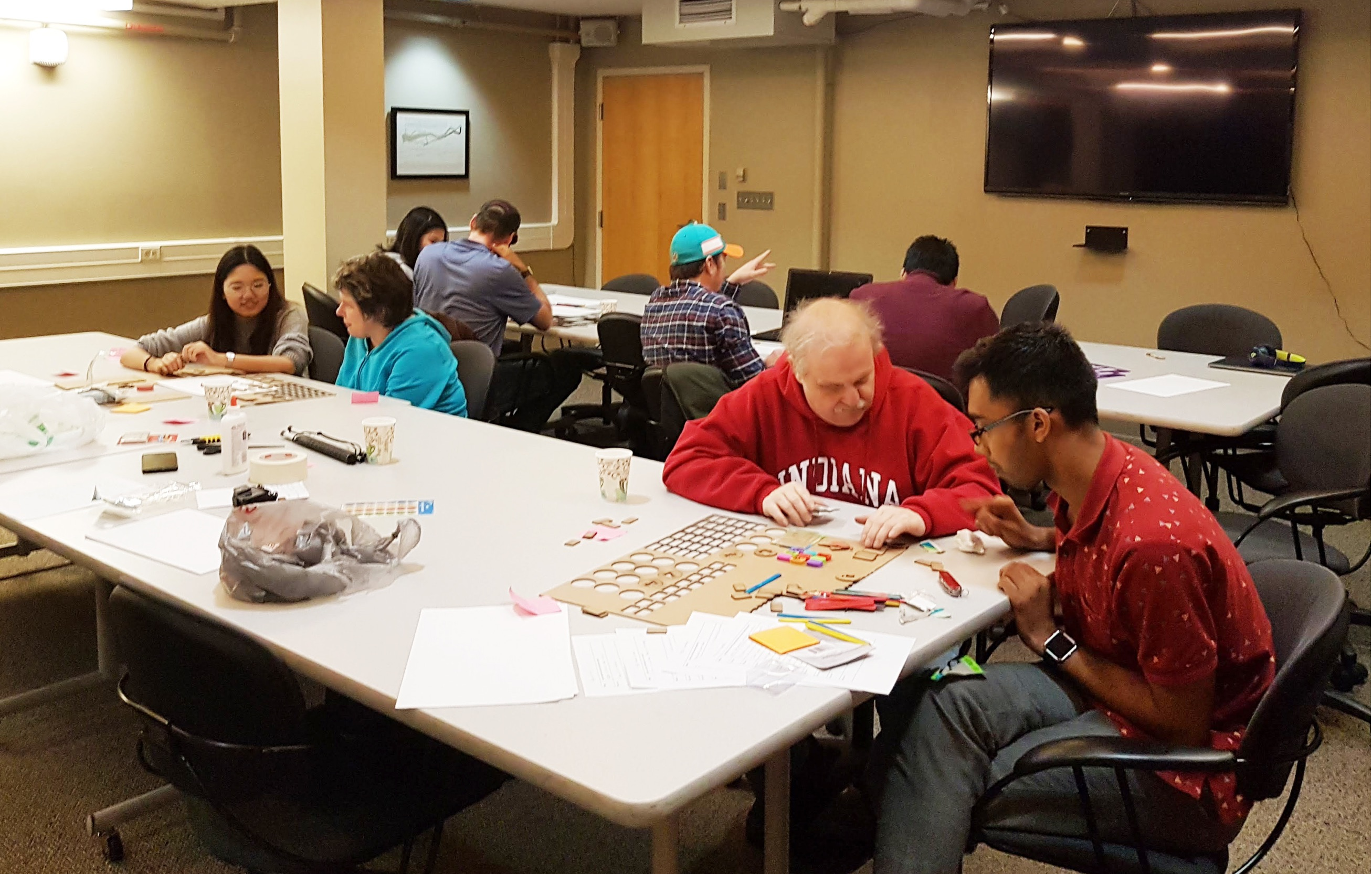 Image showing four visually impaired participants participating in Co-Design workshop where they are creating concepts with design students.