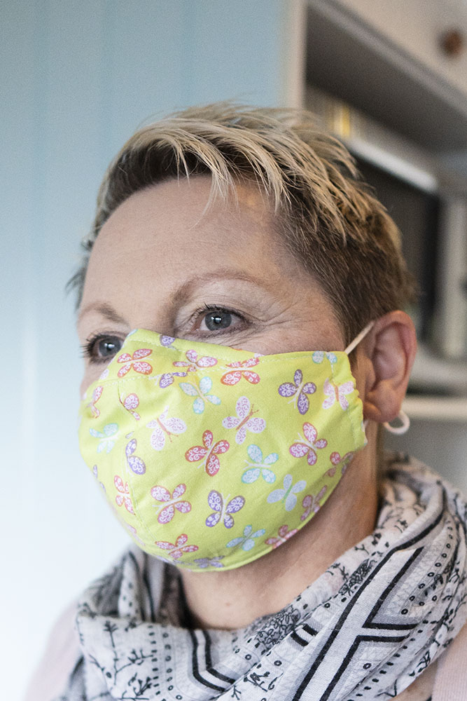 Woman Wearing Lime Green Face Mask With Butterfiles