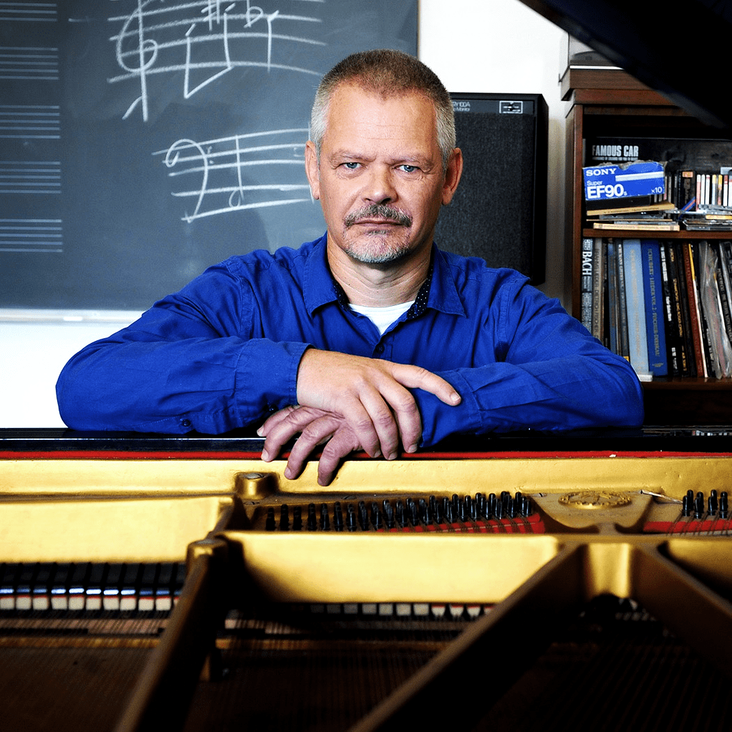 South African composer Hendrik Hofmeyr sitting at his grand piano at the South African College of Music.