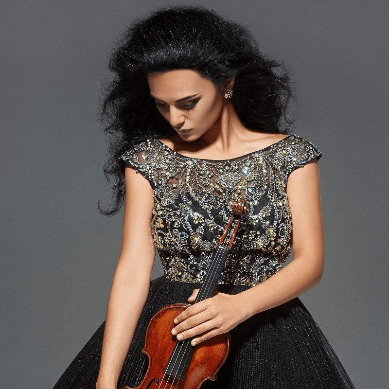 Dr. Nune Melik, international concert violinist, holding her violin.