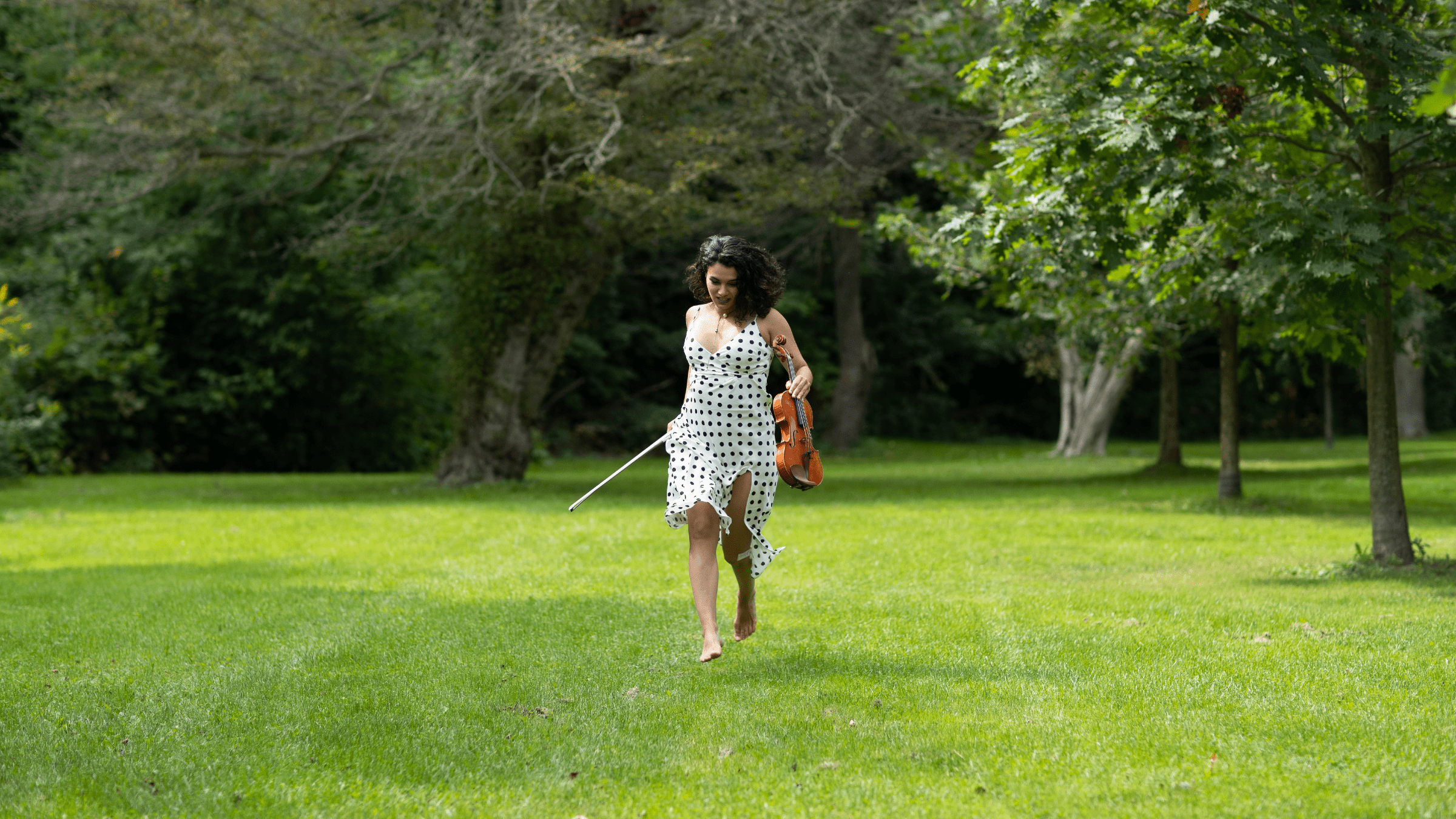 Female concert violinist Nune Melik running in a beautiful Serbian field.