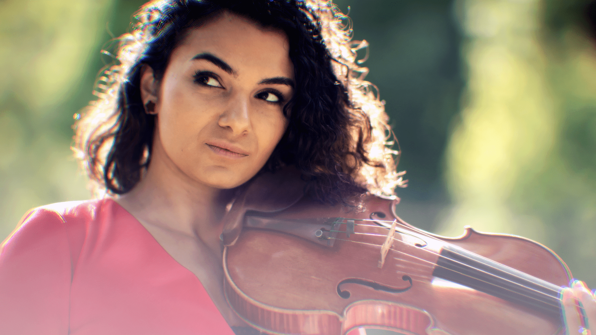 Beautiful female classical violinist Nune Melik holding her violin with a meadow in the background.