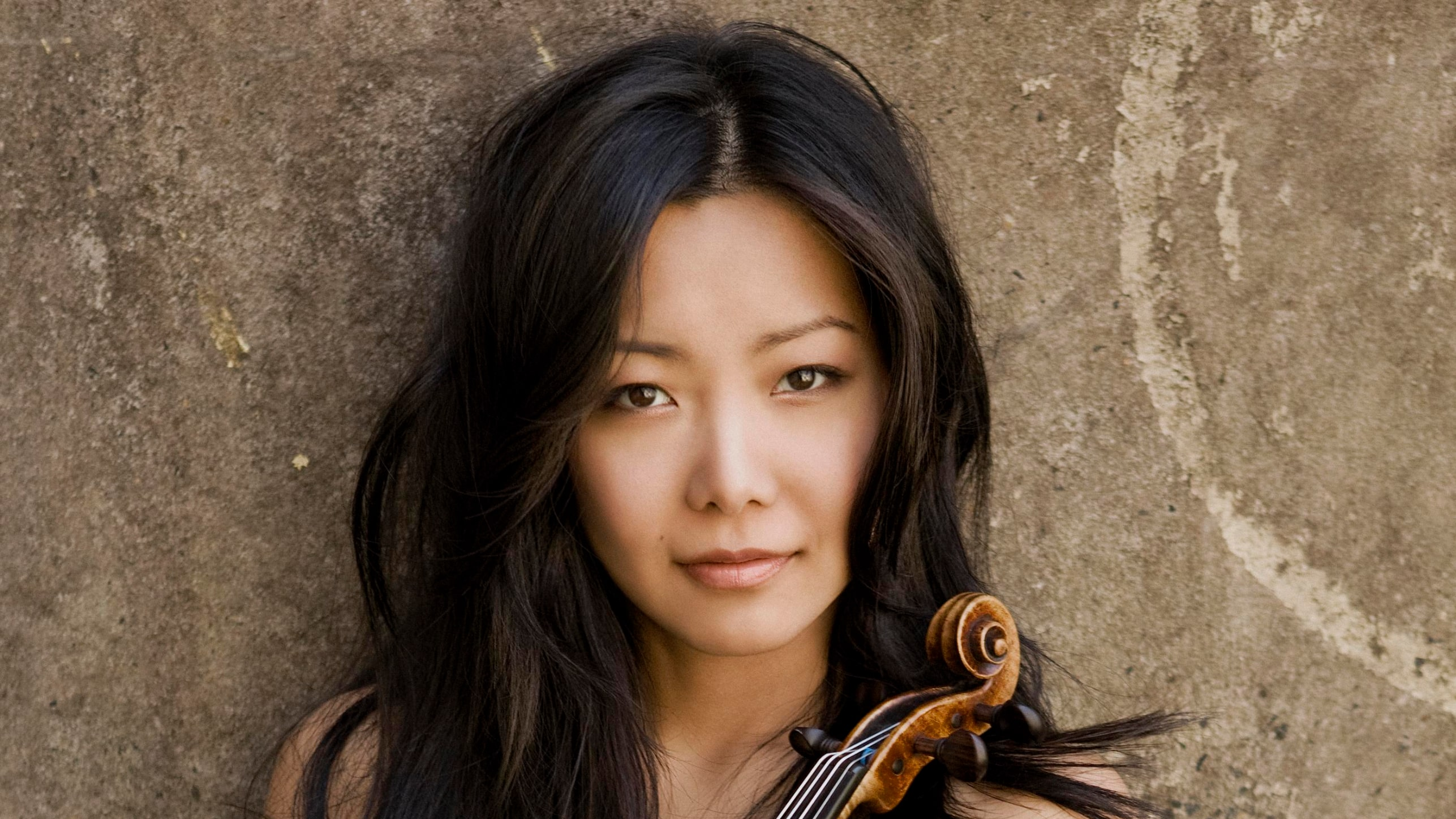 A violinist (Susanne Hou) holding her violin sitting against a stone wall.