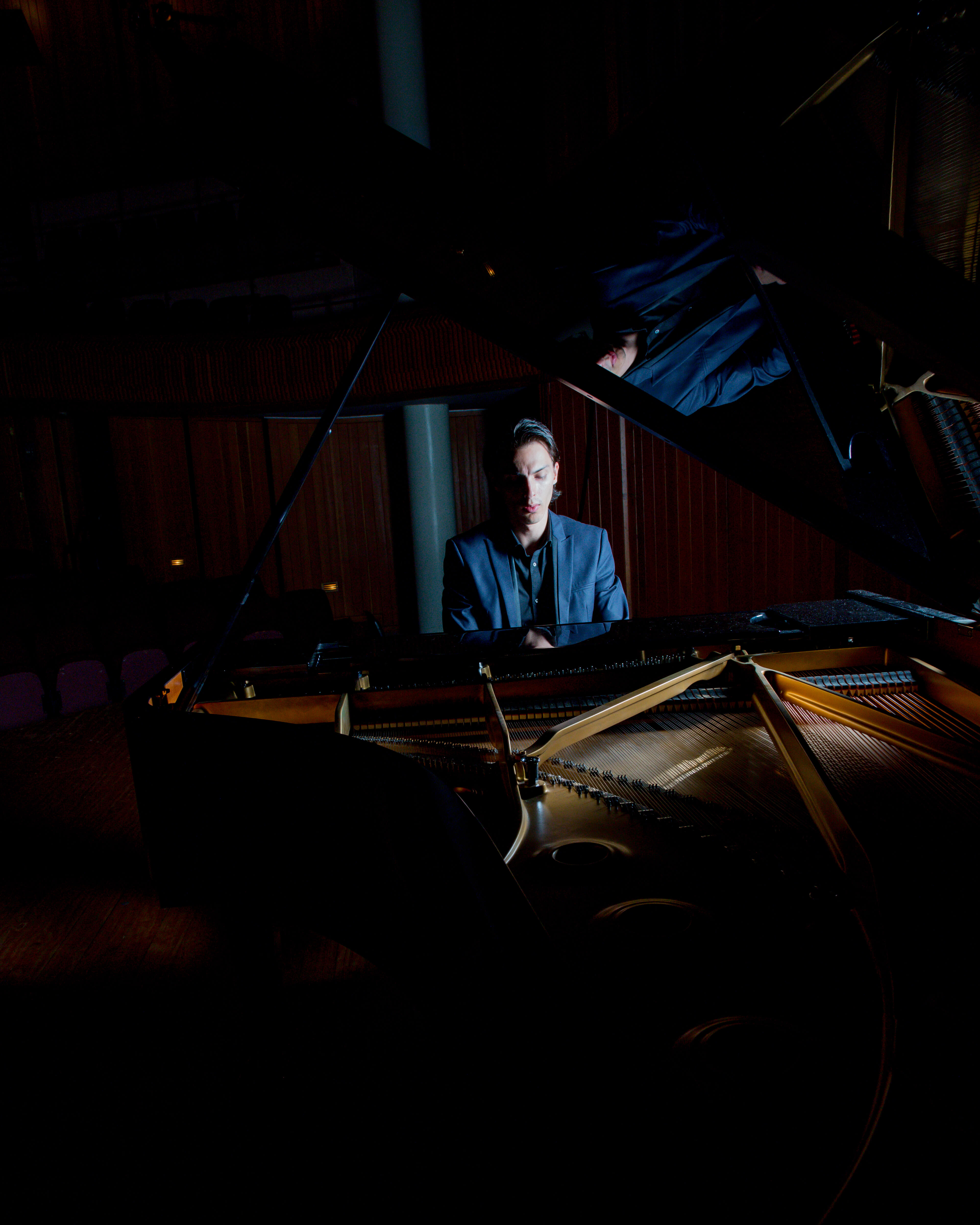 A pianist sitting at a grand, photographed through the lid of the piano