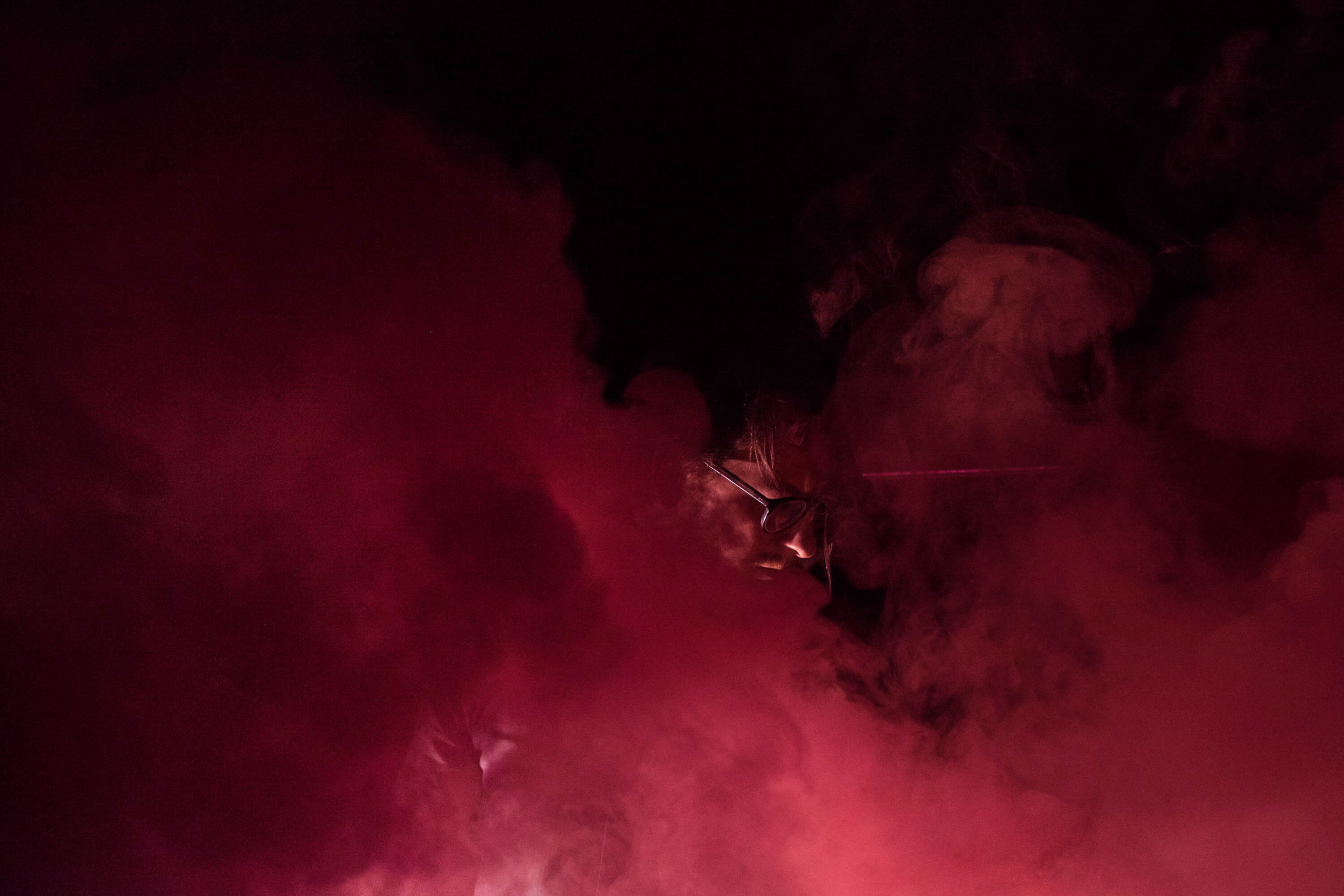 Producer, composer and musician Nicolas Bernier standing in red smoke with glasses.