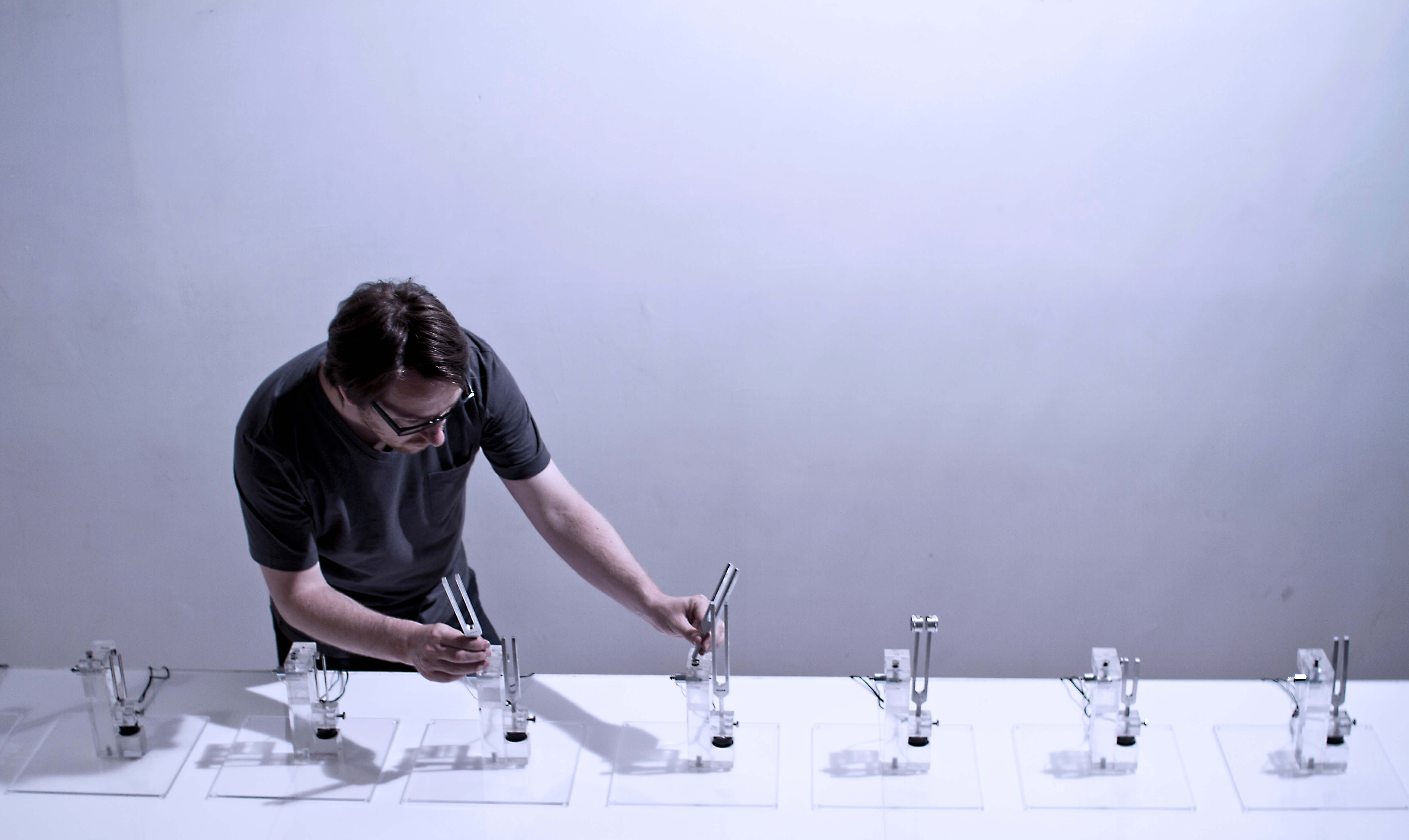 Nicolas Bernier playing with several tuning forks on a white table.