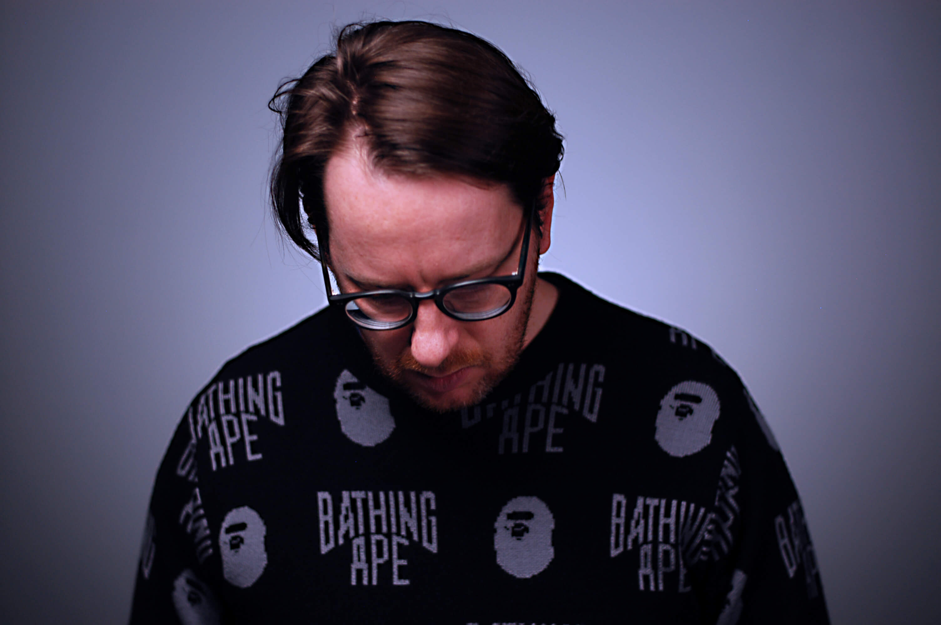 Composer Nicolas Bernier staring at the floor in a cool bathing ape t shirt.
