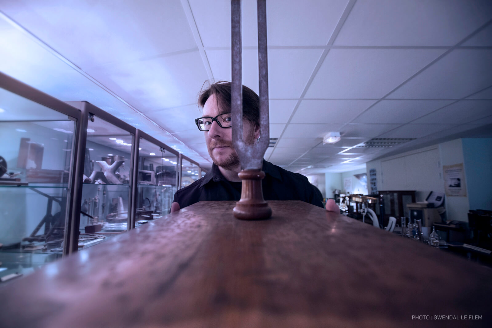 Composer and producer of electronic music, Nicolas Bernier, standing behind a tuning fork which is on a table.