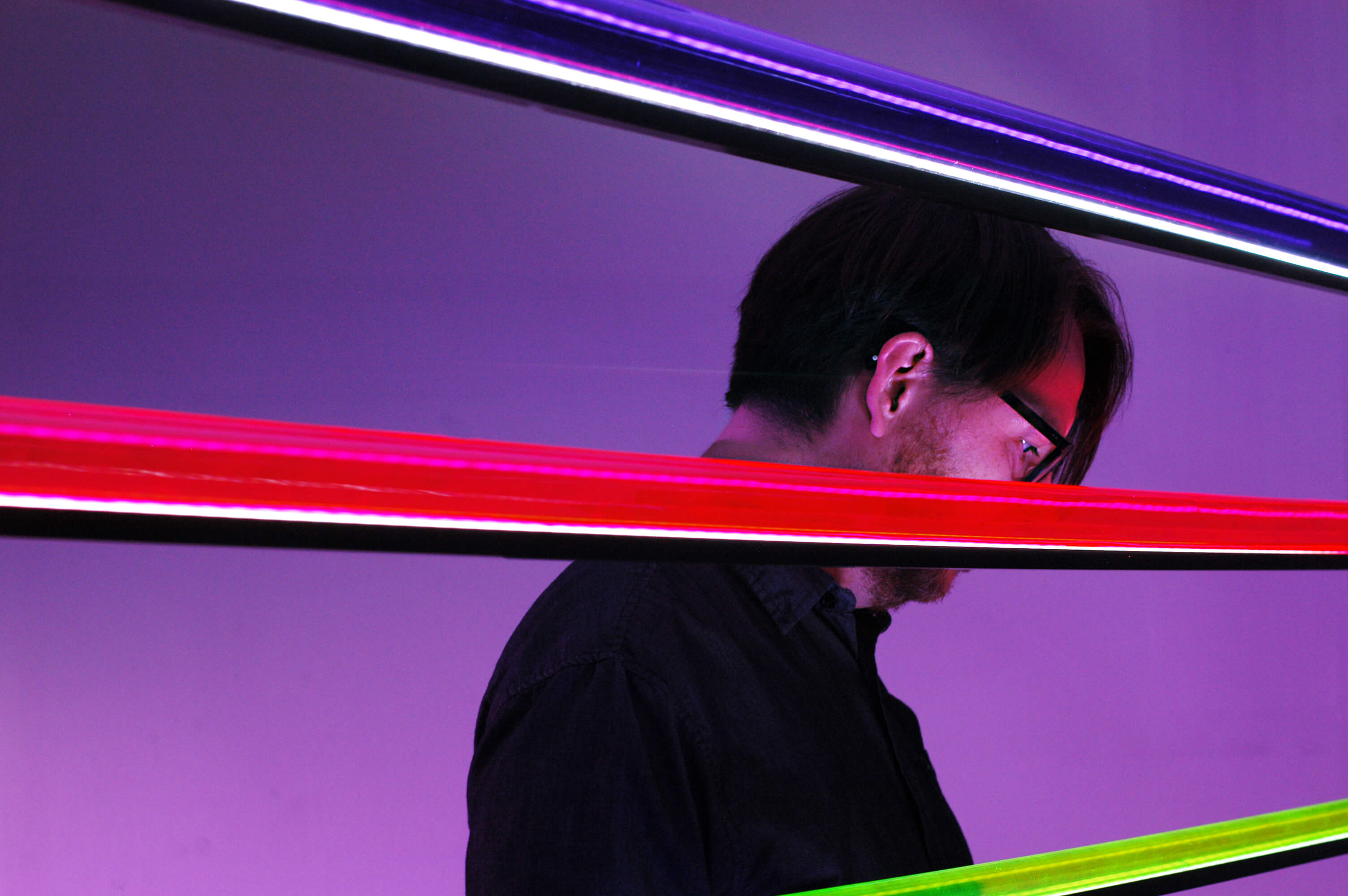 Nicolas Bernier standing in a purple room with three bar lights.