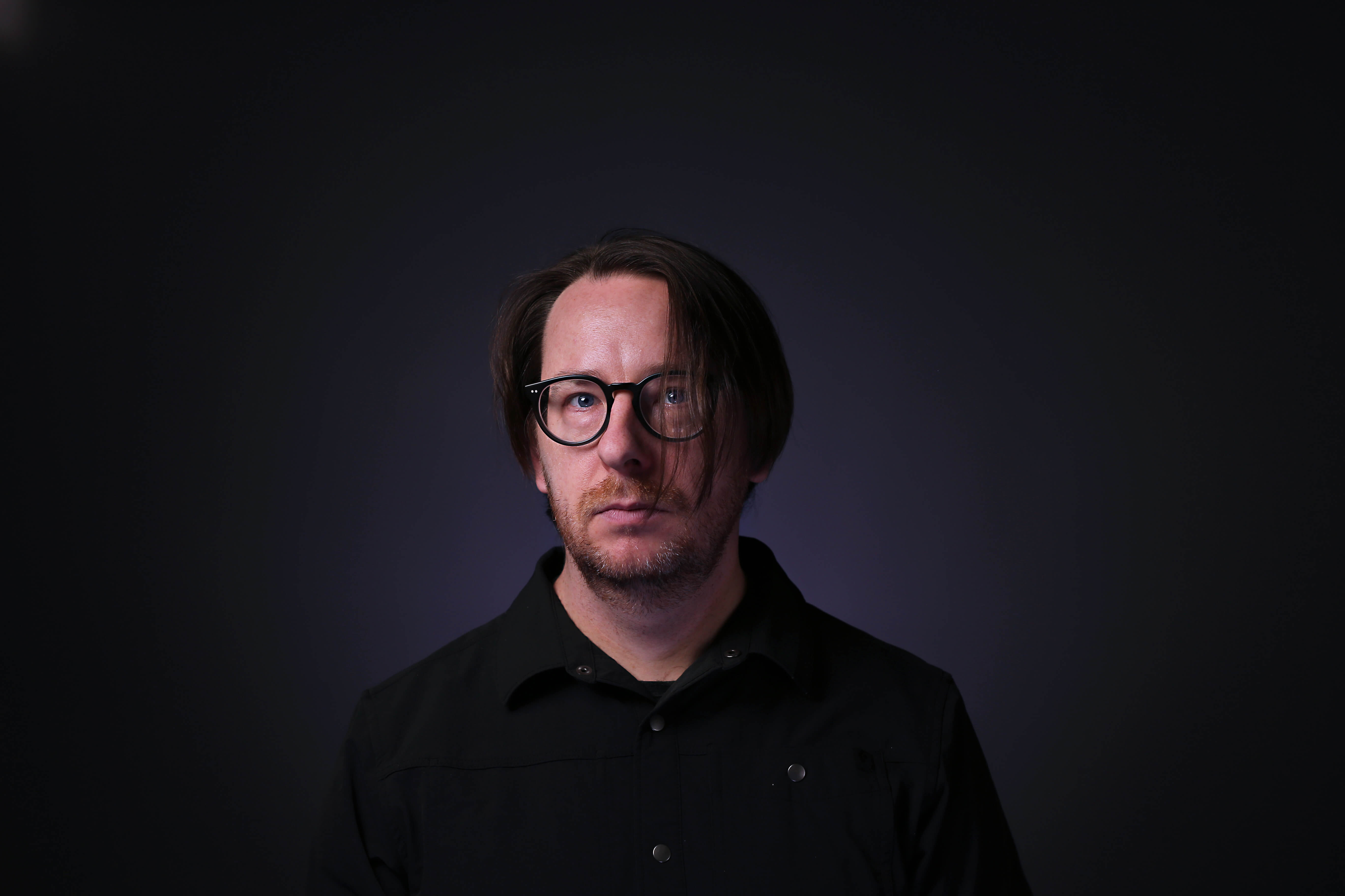A composer standing in front of a black background with glasses.