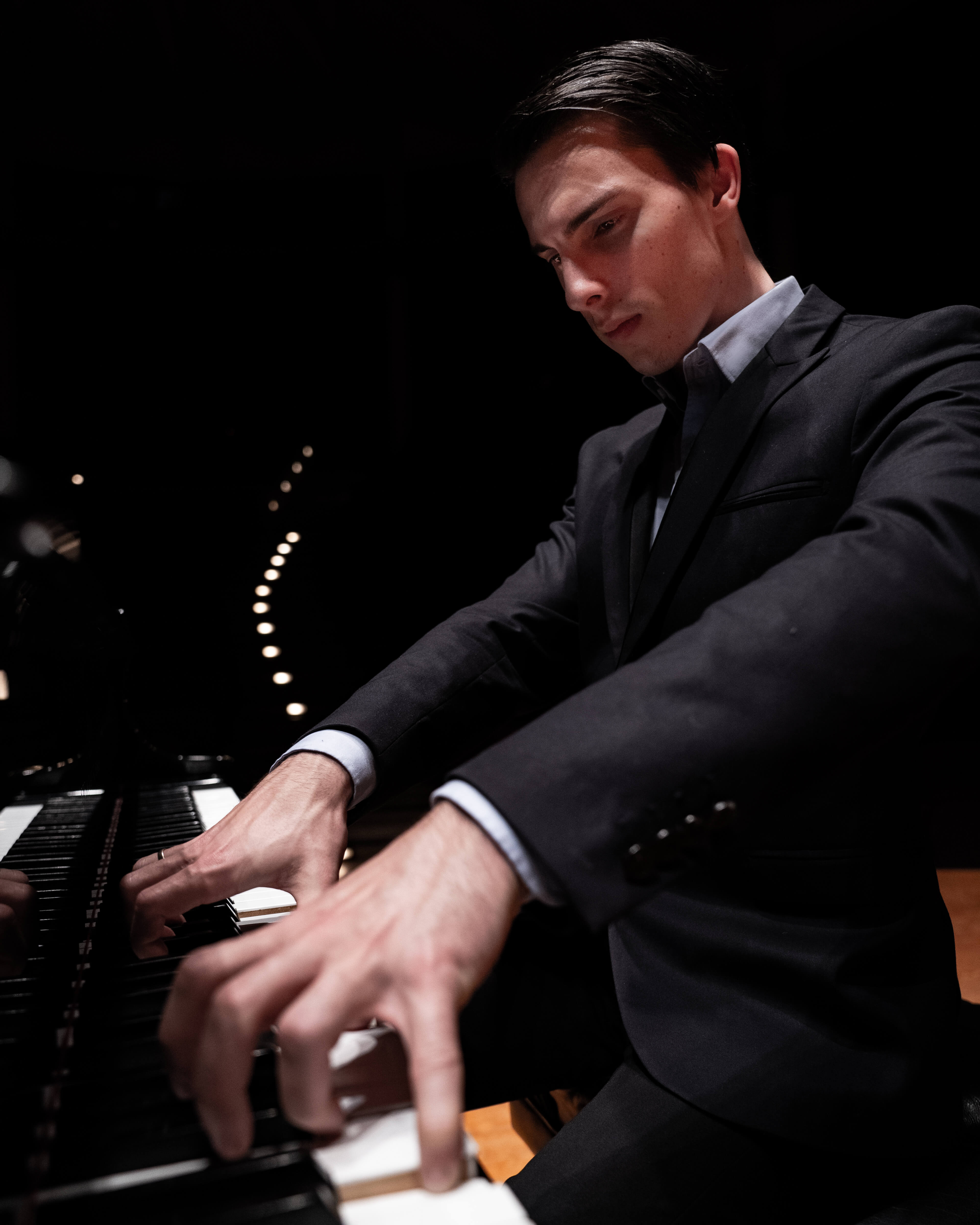 A pianist playing with curled fingers from an interesting angle.
