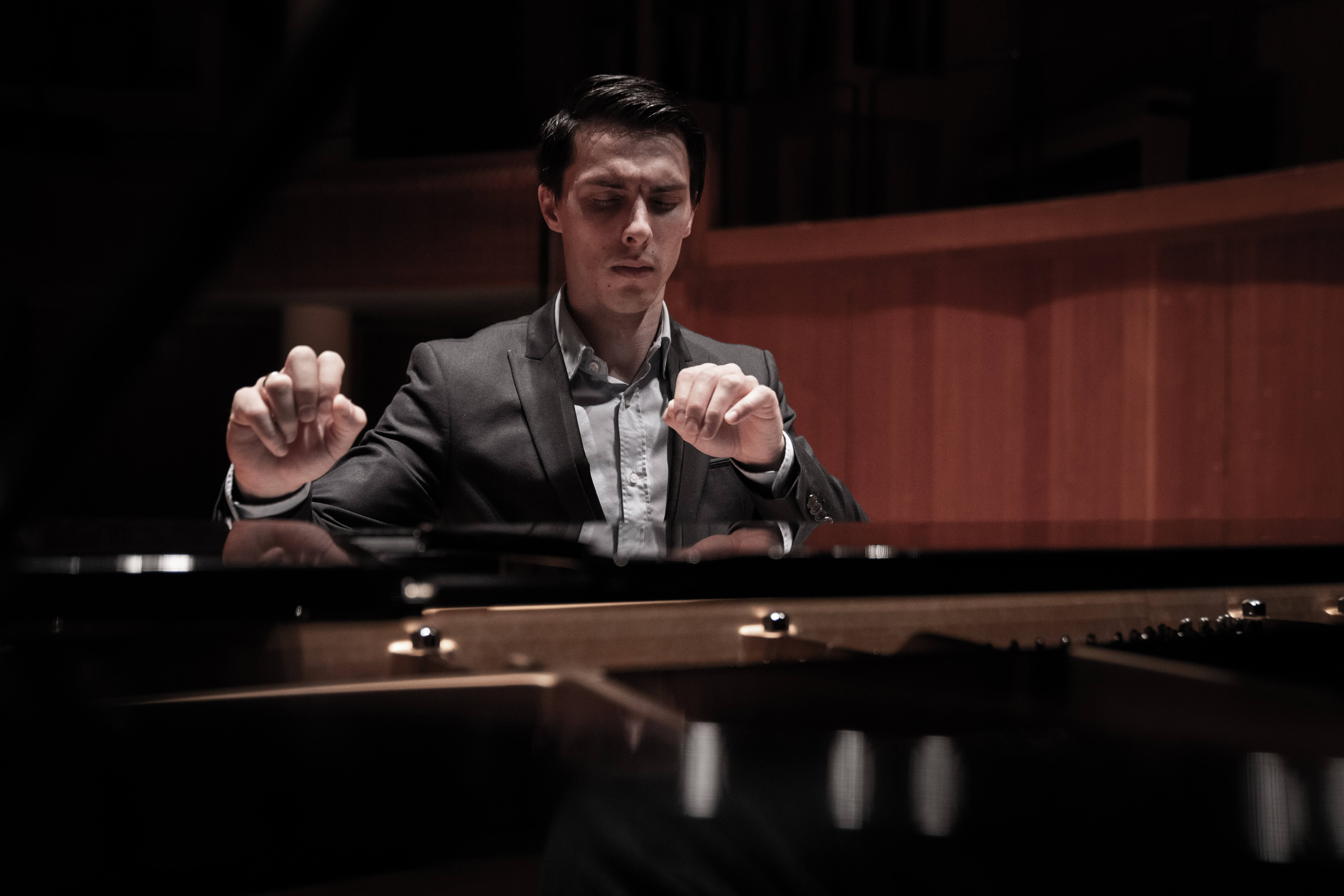 A pianist playing with his hands flying in the air.