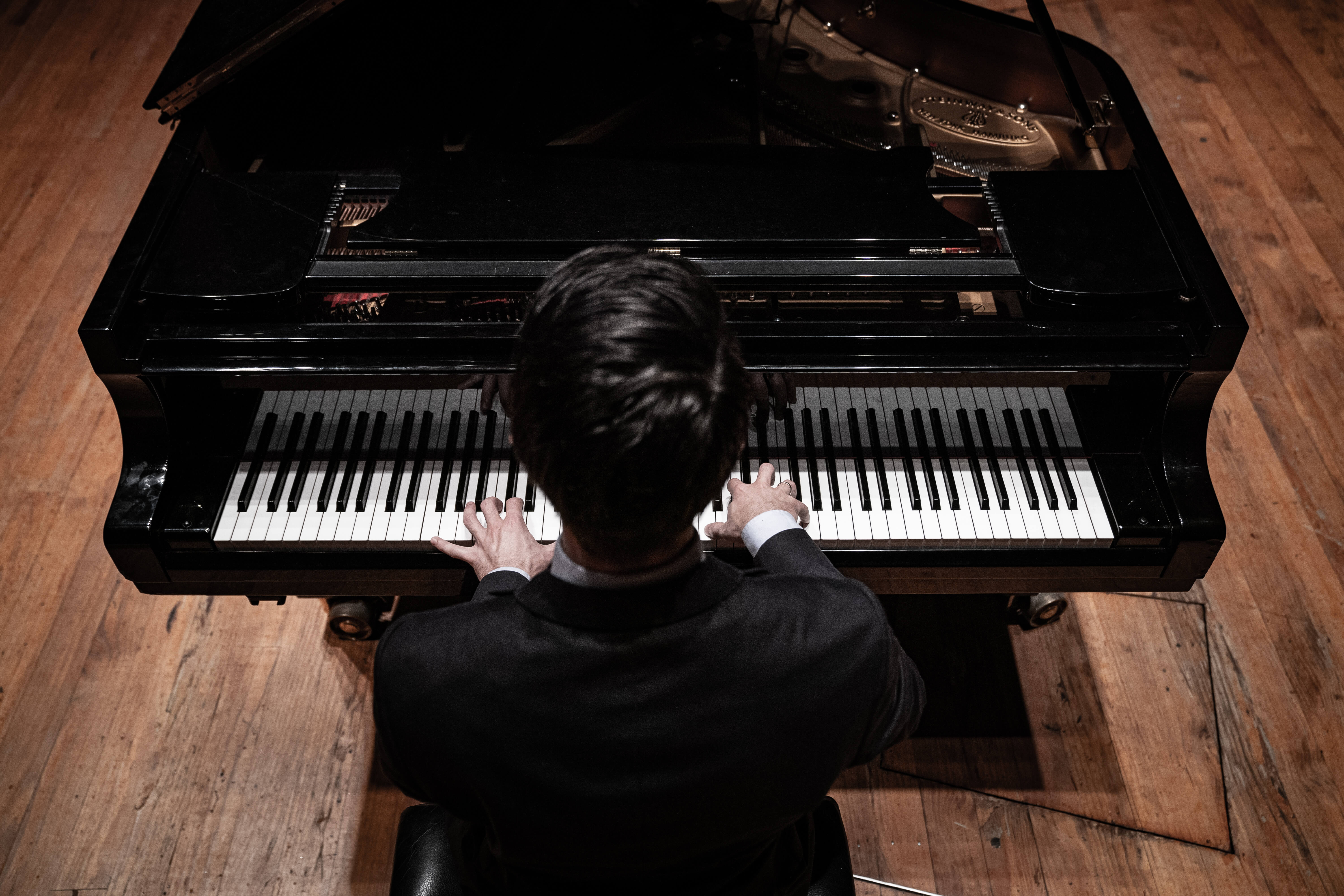 Pianist from above playing a Steinway grand piano.