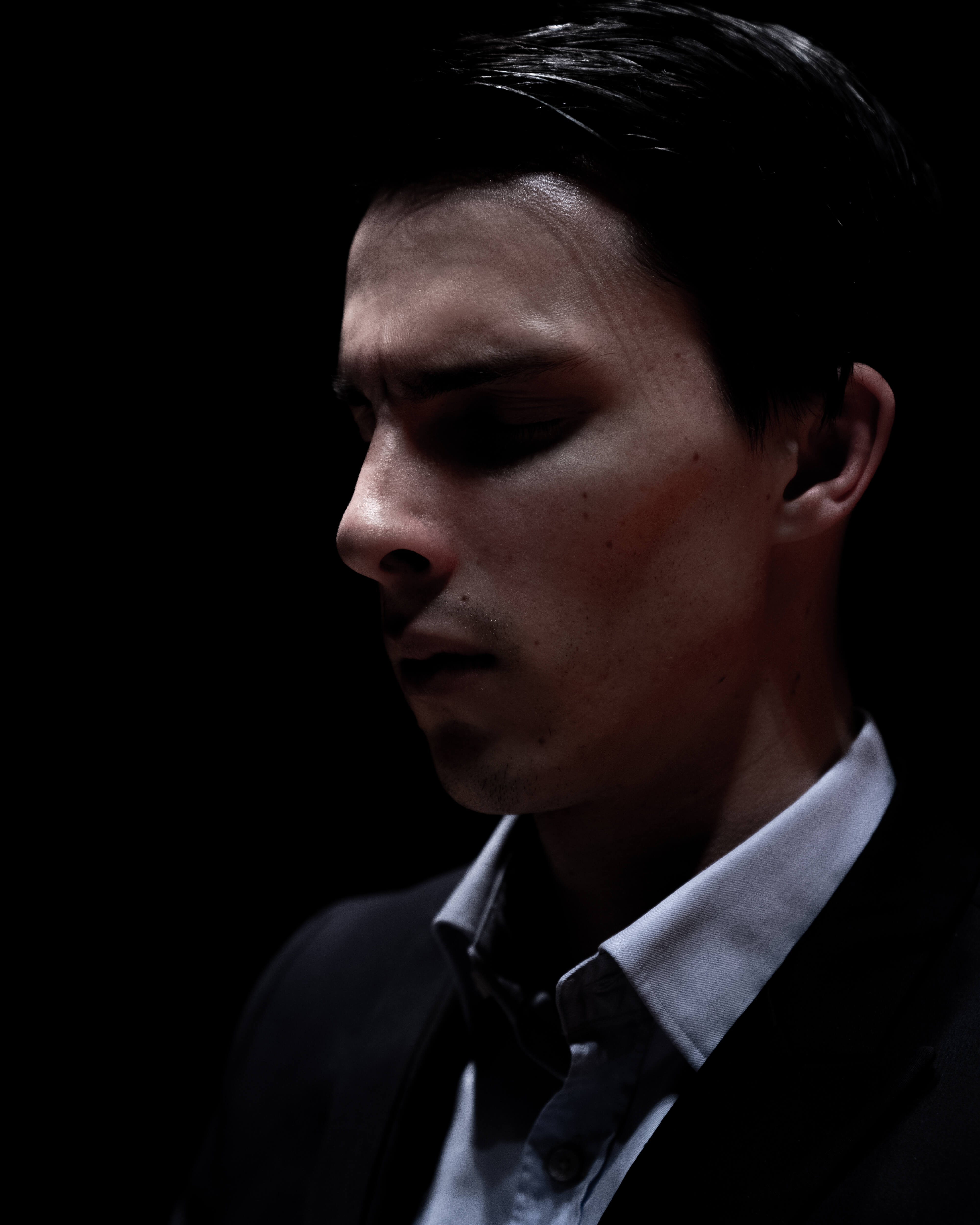 A portrait of a young man wearing a blue collared shirt an a black blazer in the dark.