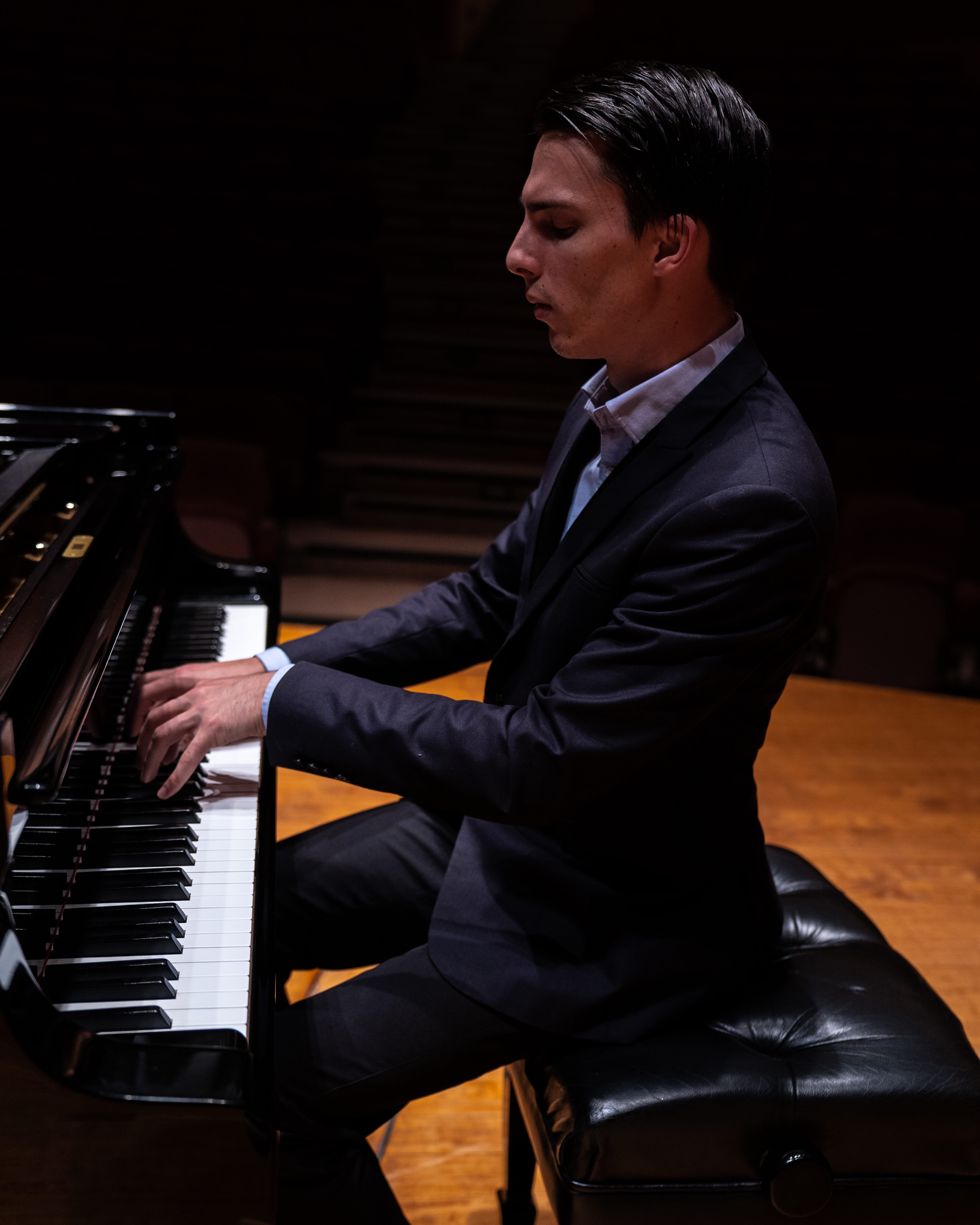 A pianist with curled fingers playing a grand piano in a dark room