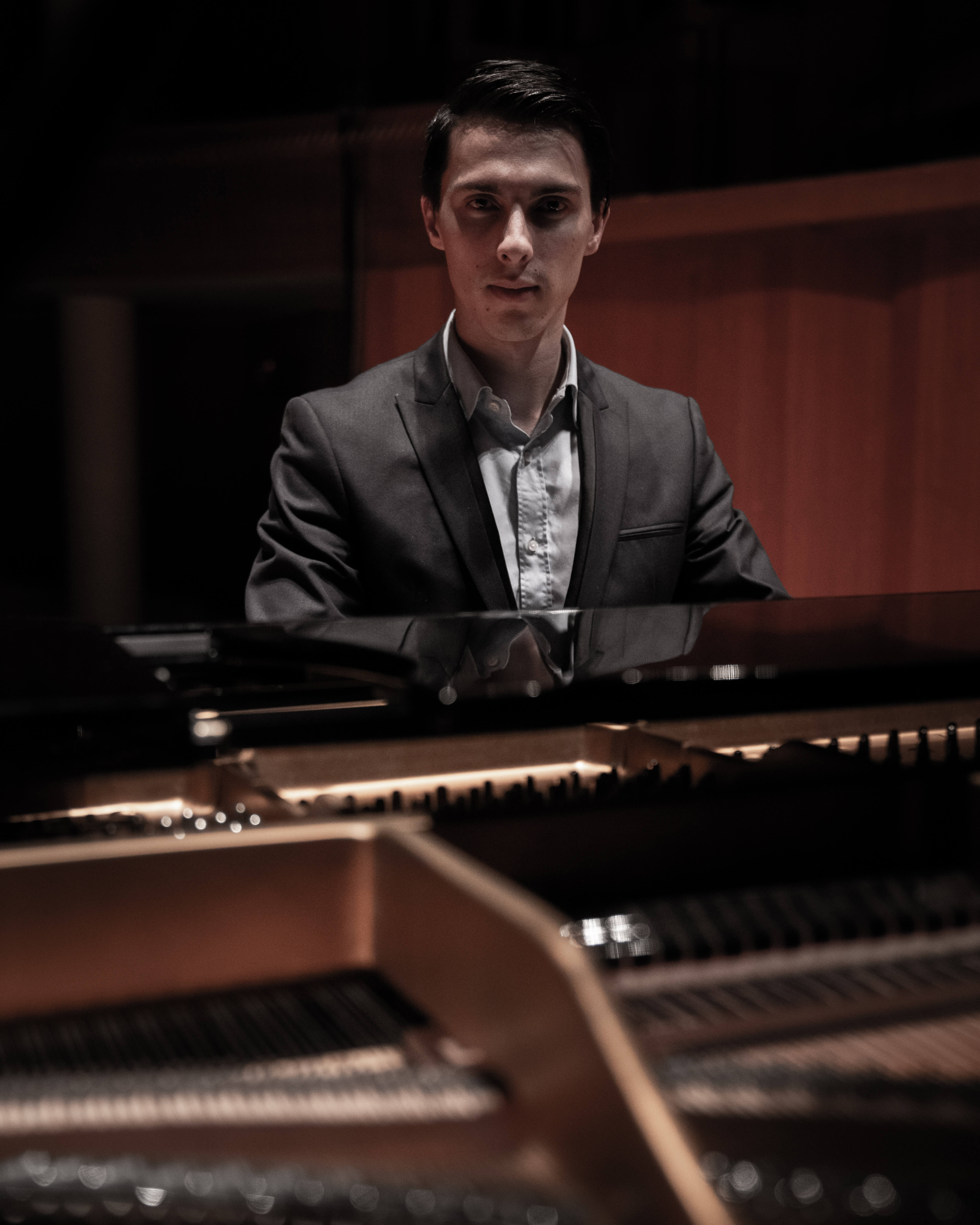 A pianist photographed through the lid of a grand Steinway & Sons piano.
