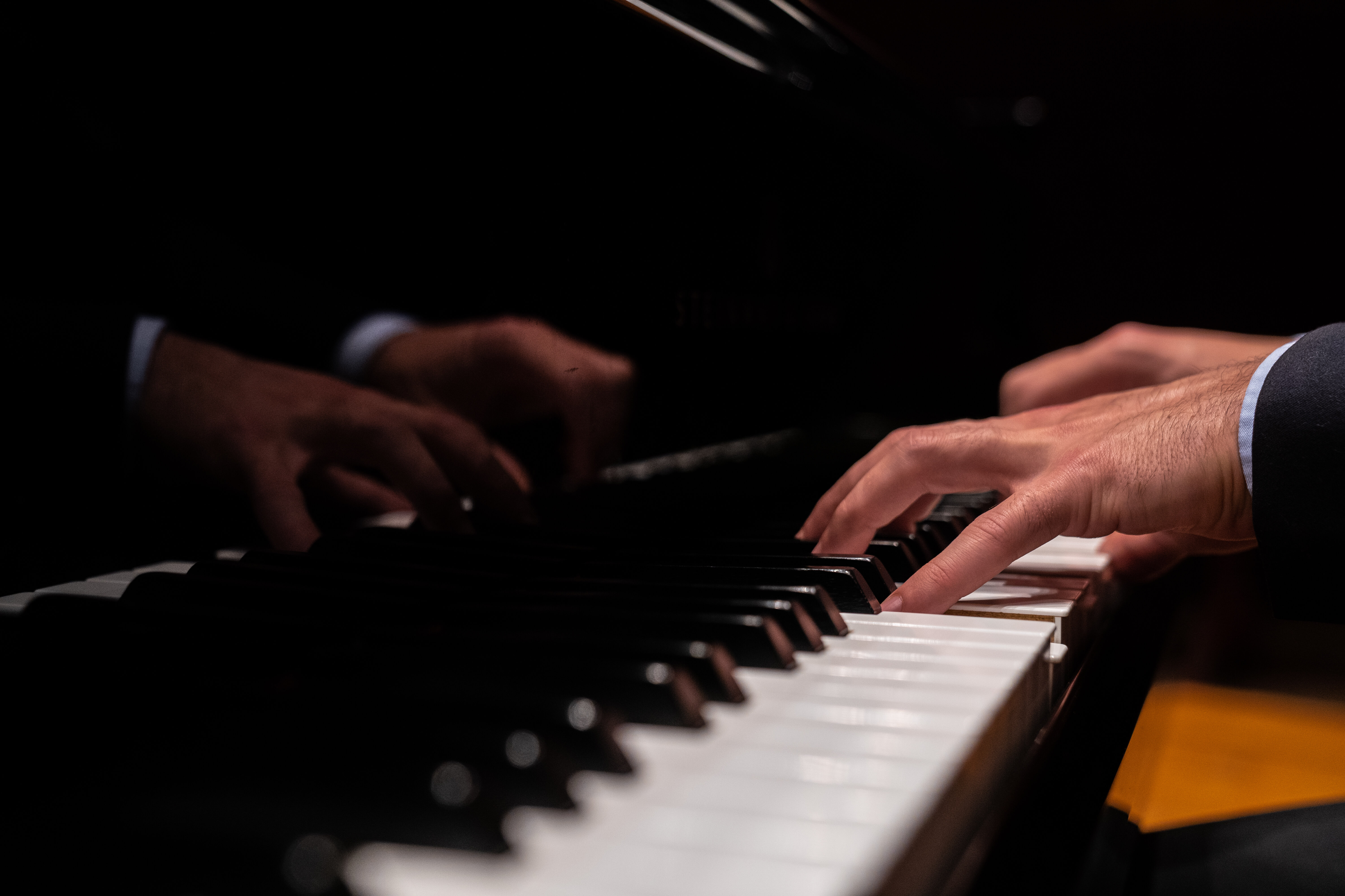 The hands of a pianist reflected in the lid of a black grand piano.