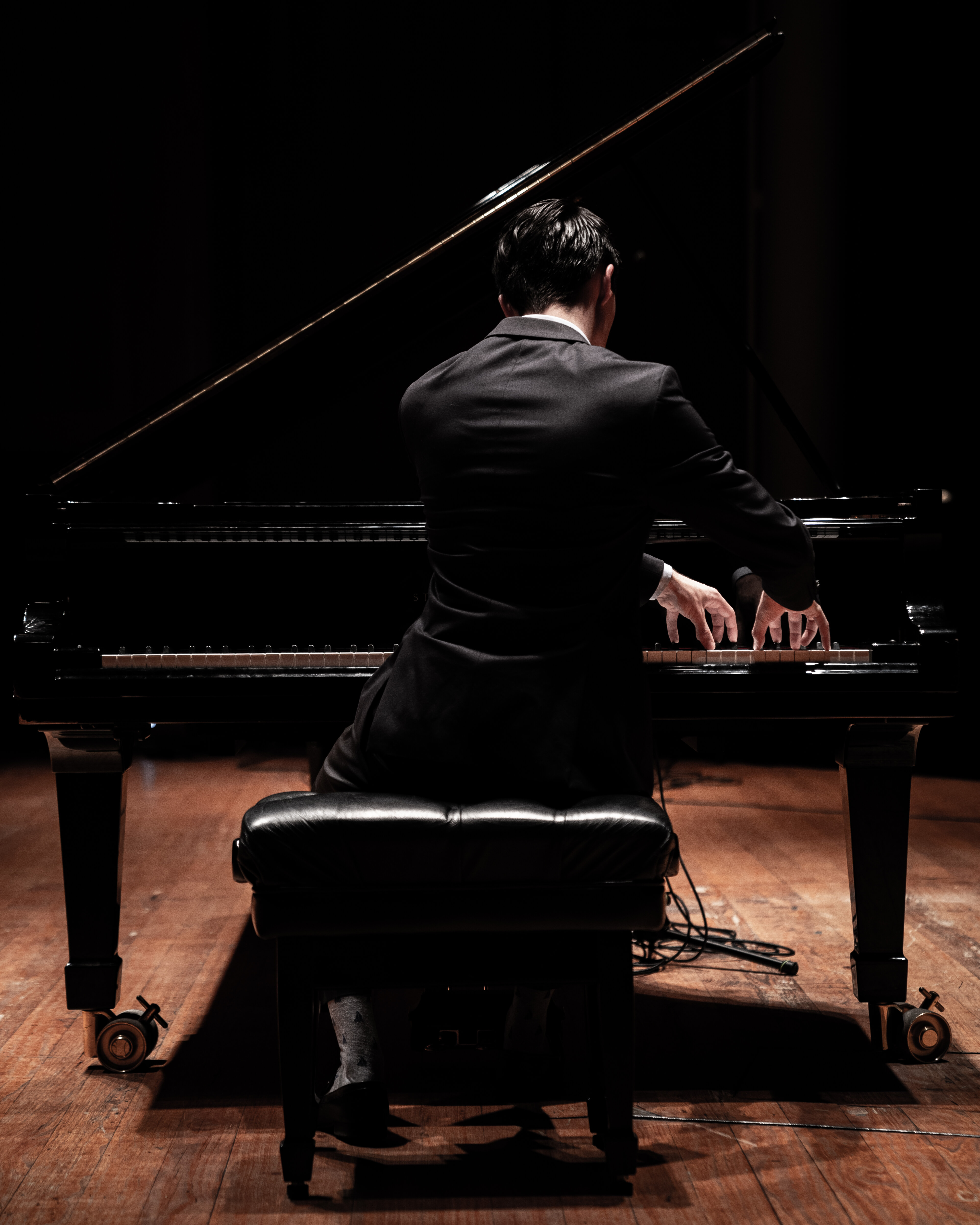 Pianist from behind playing a grand piano with excellent technique.