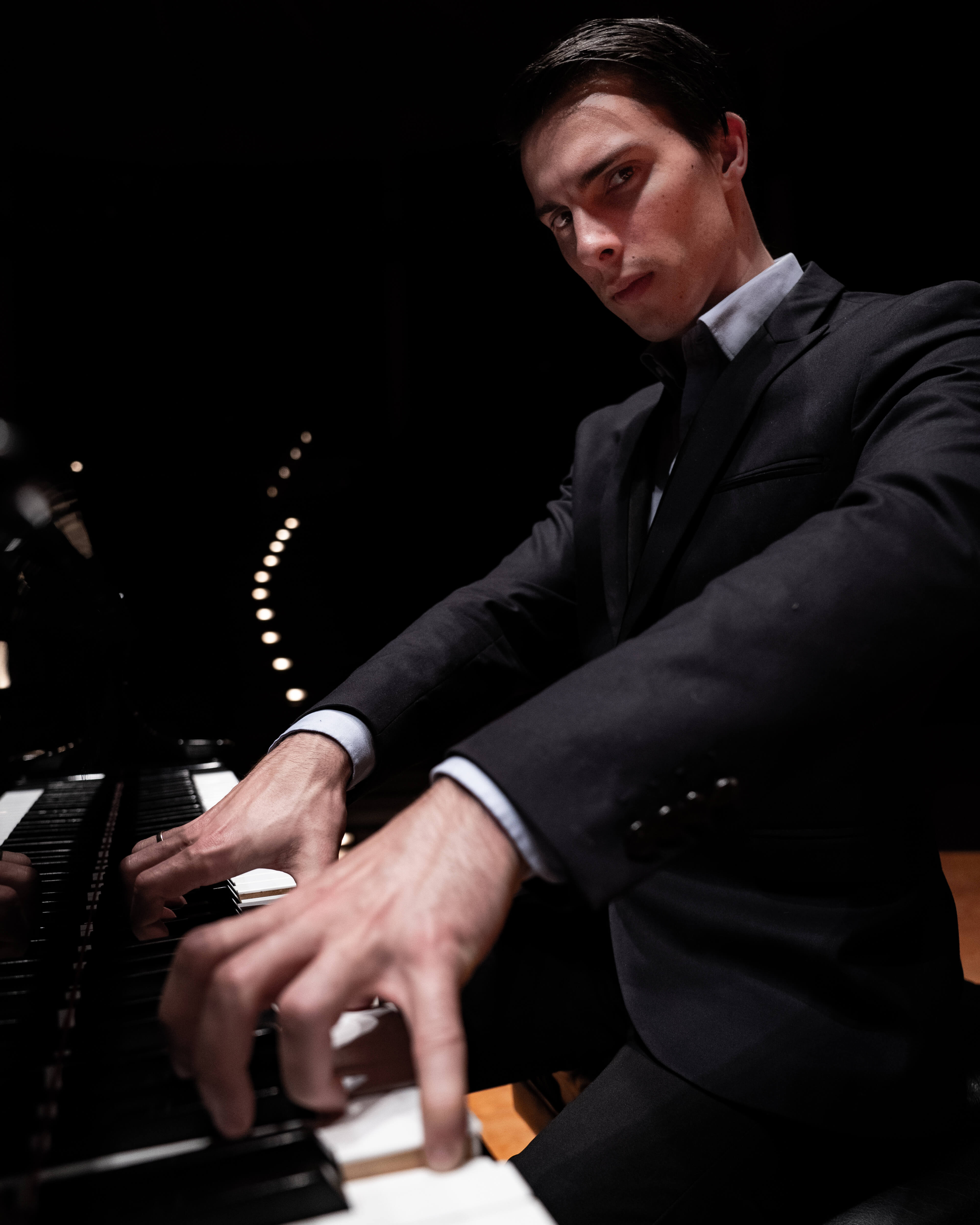 A pianist with curled fingers playing the piano and looking at the camera.