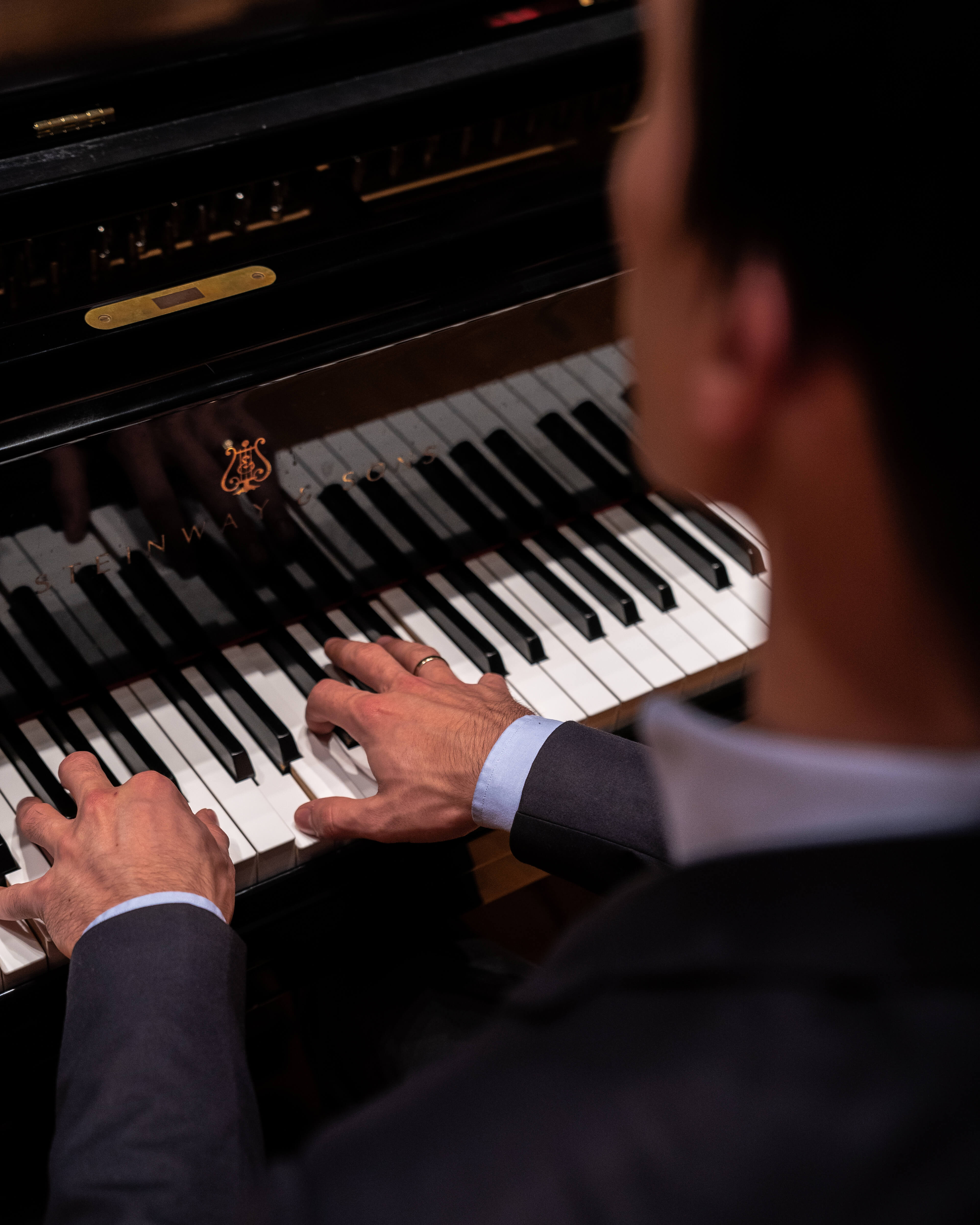 An over the shoulder photo of a pianist playing a Steinway and Sons grand piano.