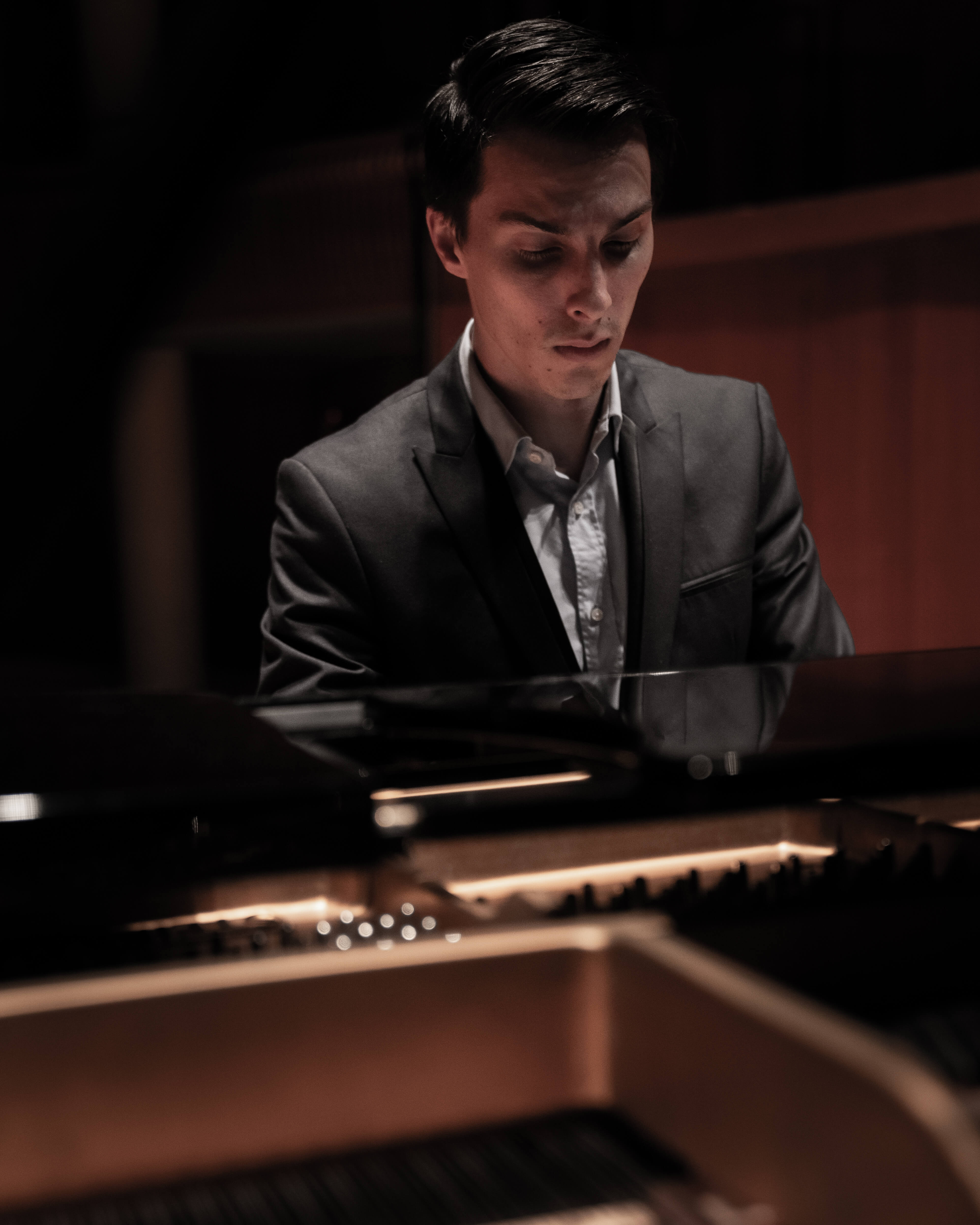 Liam Pitcher playing a Steinway and Sons grand piano in the Baxter Concert Hall.