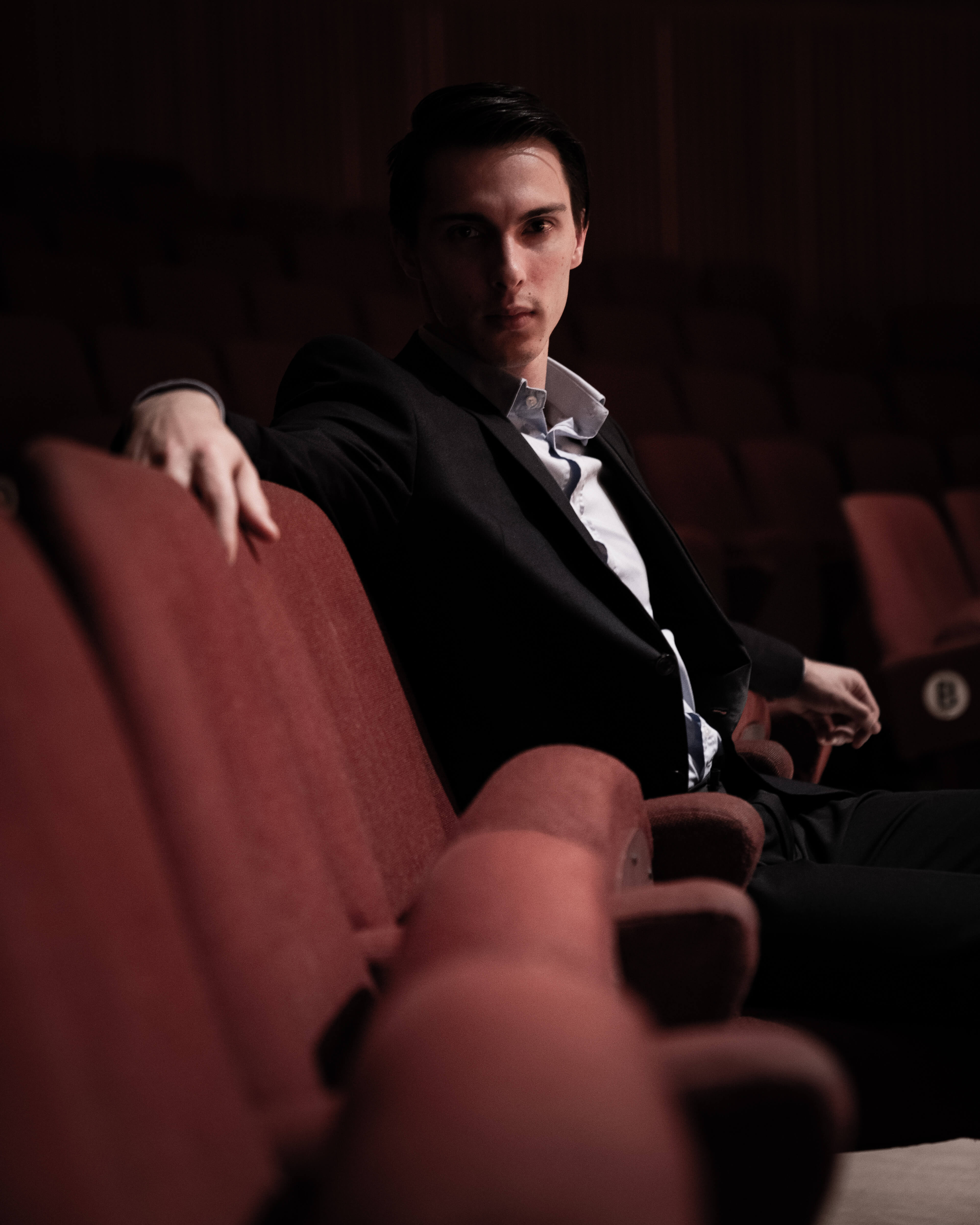 An audience member sitting in the concert hall with their arm on a red chair.