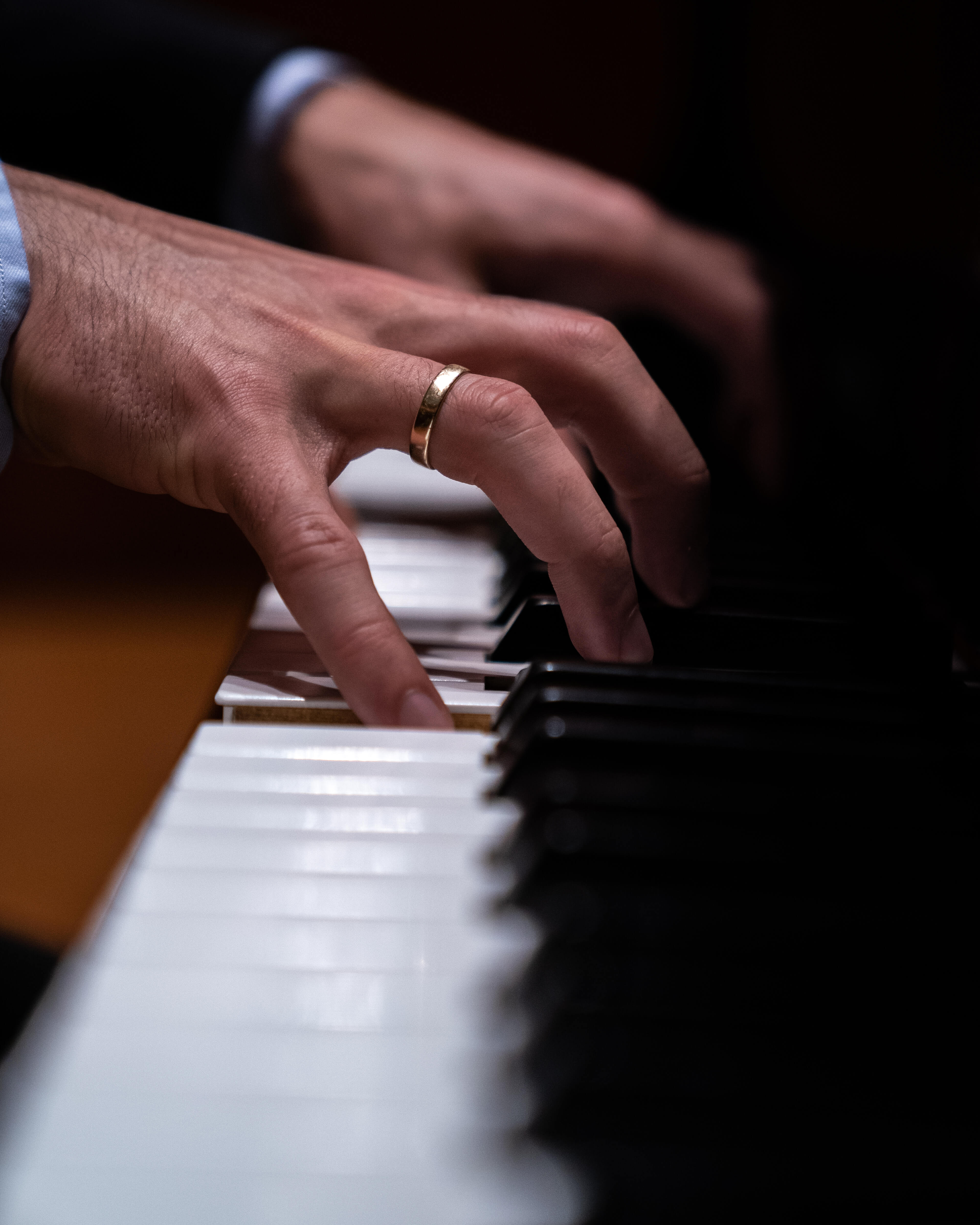 Hands with a ring playing the piano.