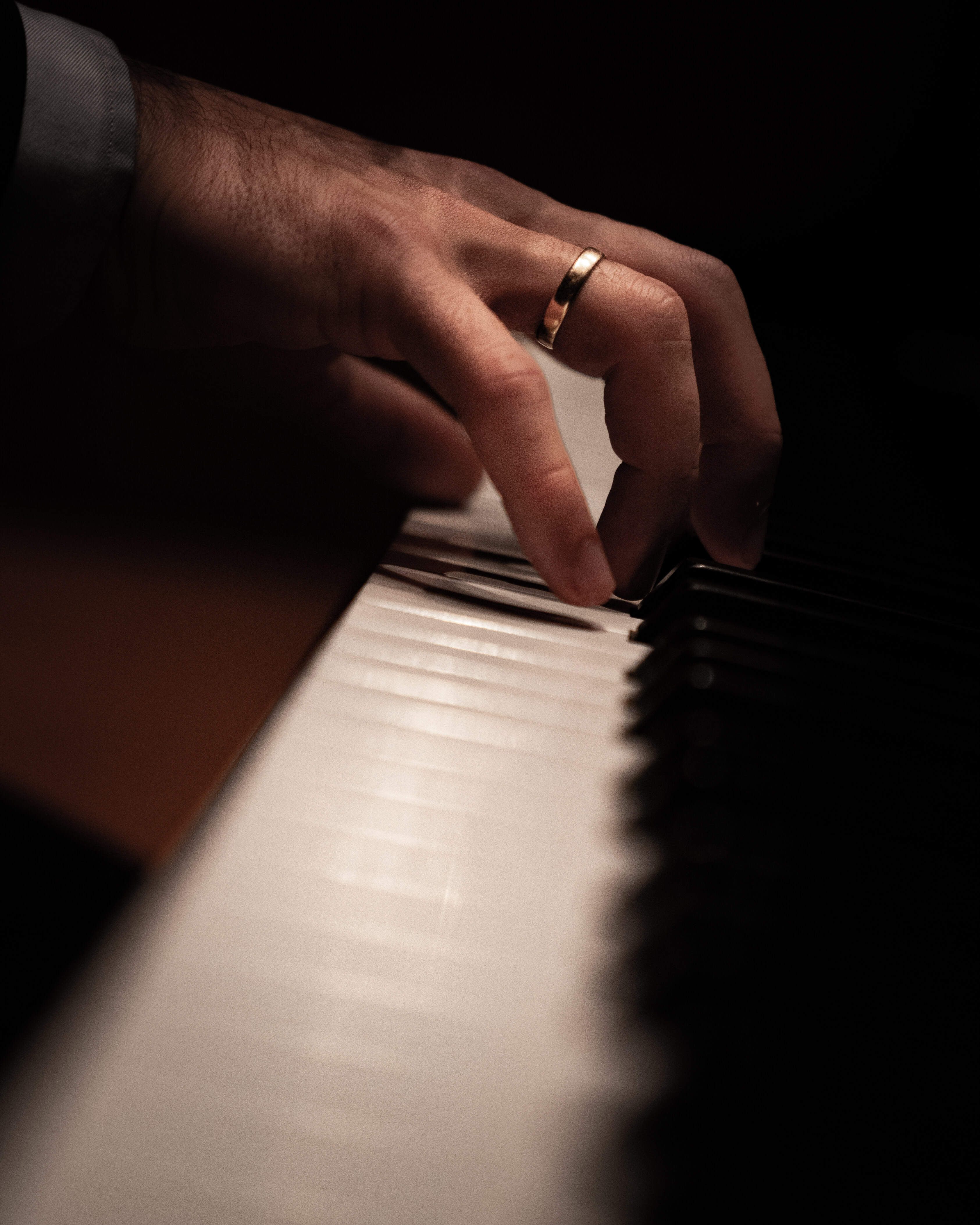A hand on piano keys with a ring on it.