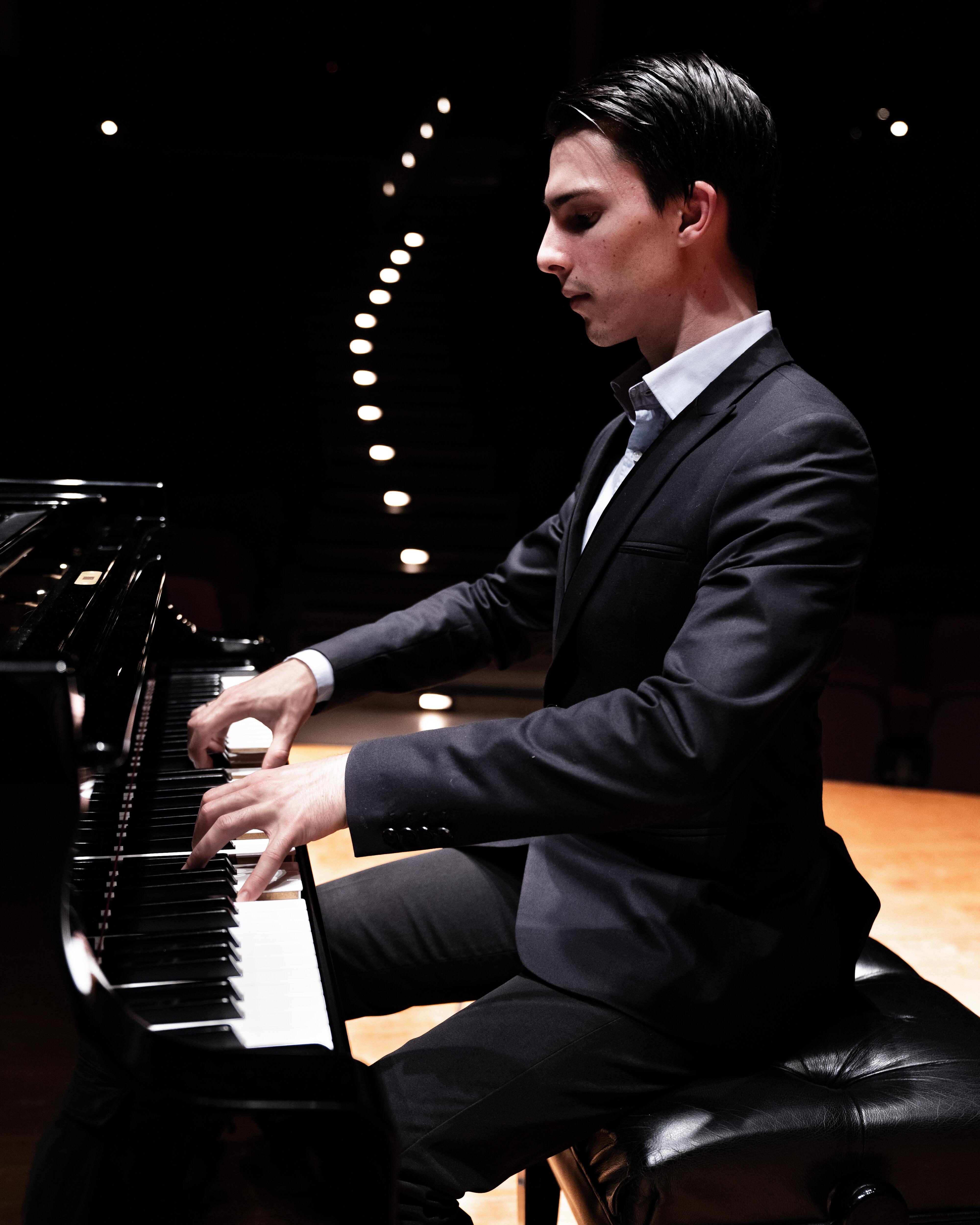 A pianist improvising at a grand Yamaha piano.