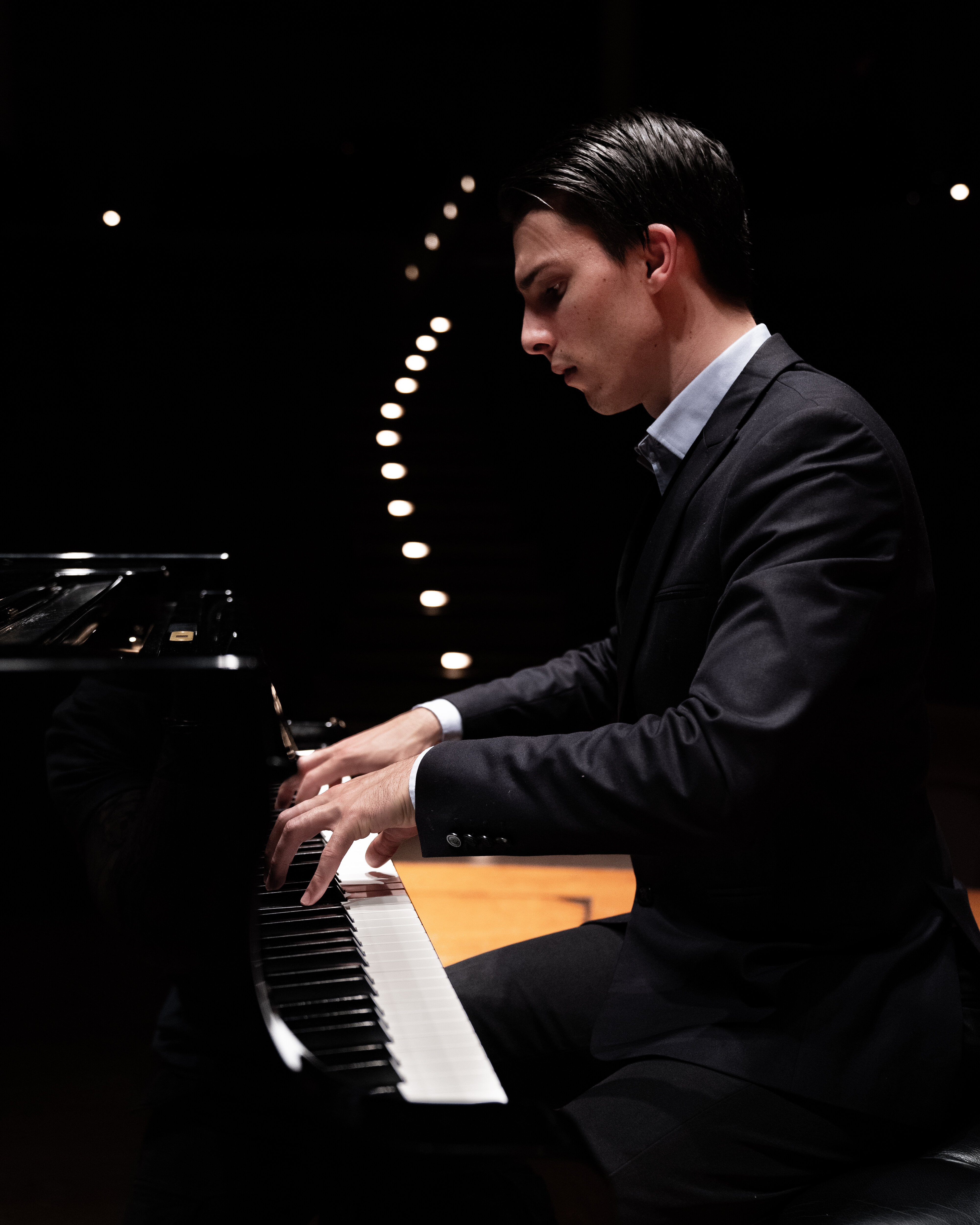 A pianist looking at his hands while playing piano in a dark concert hall.