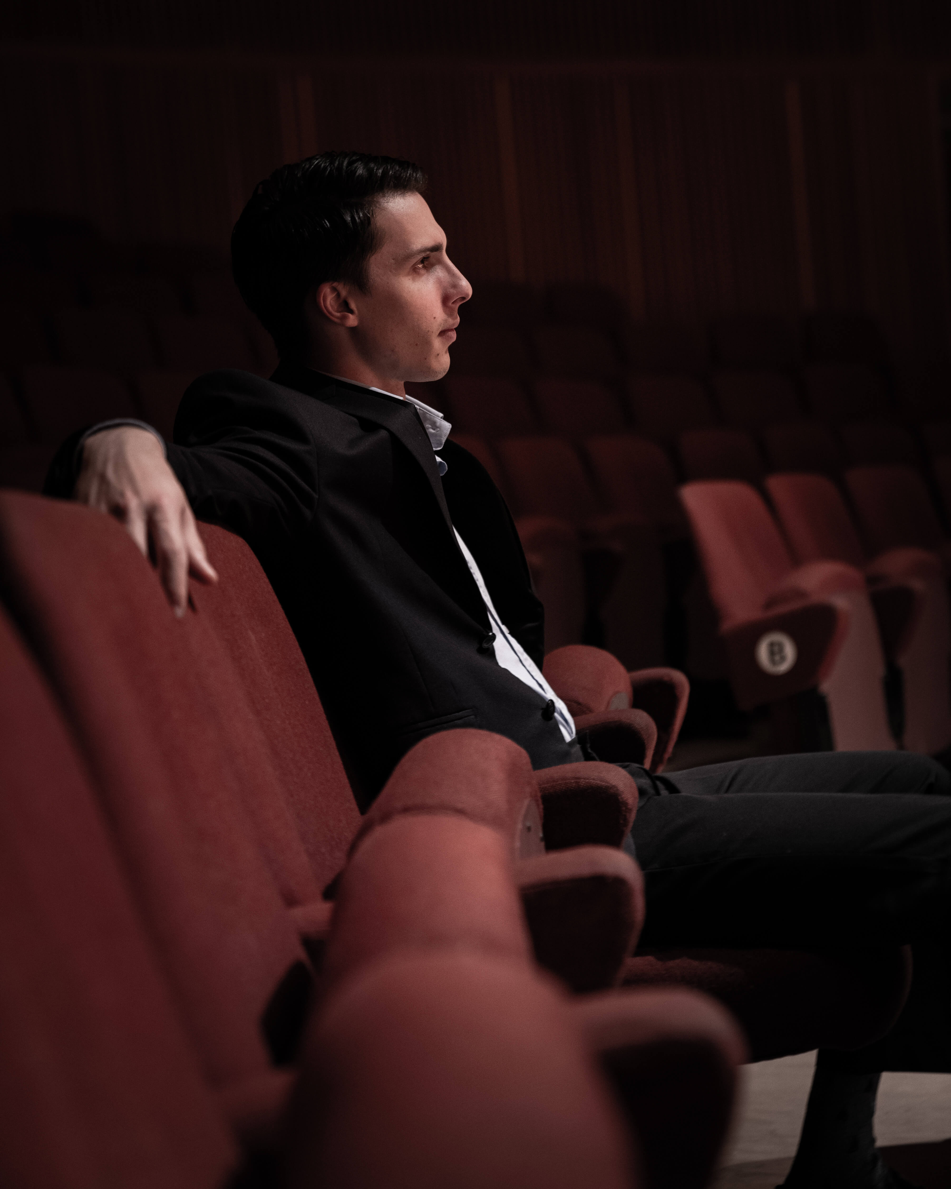 Composer sitting in concert hall with red chairs and black suit.