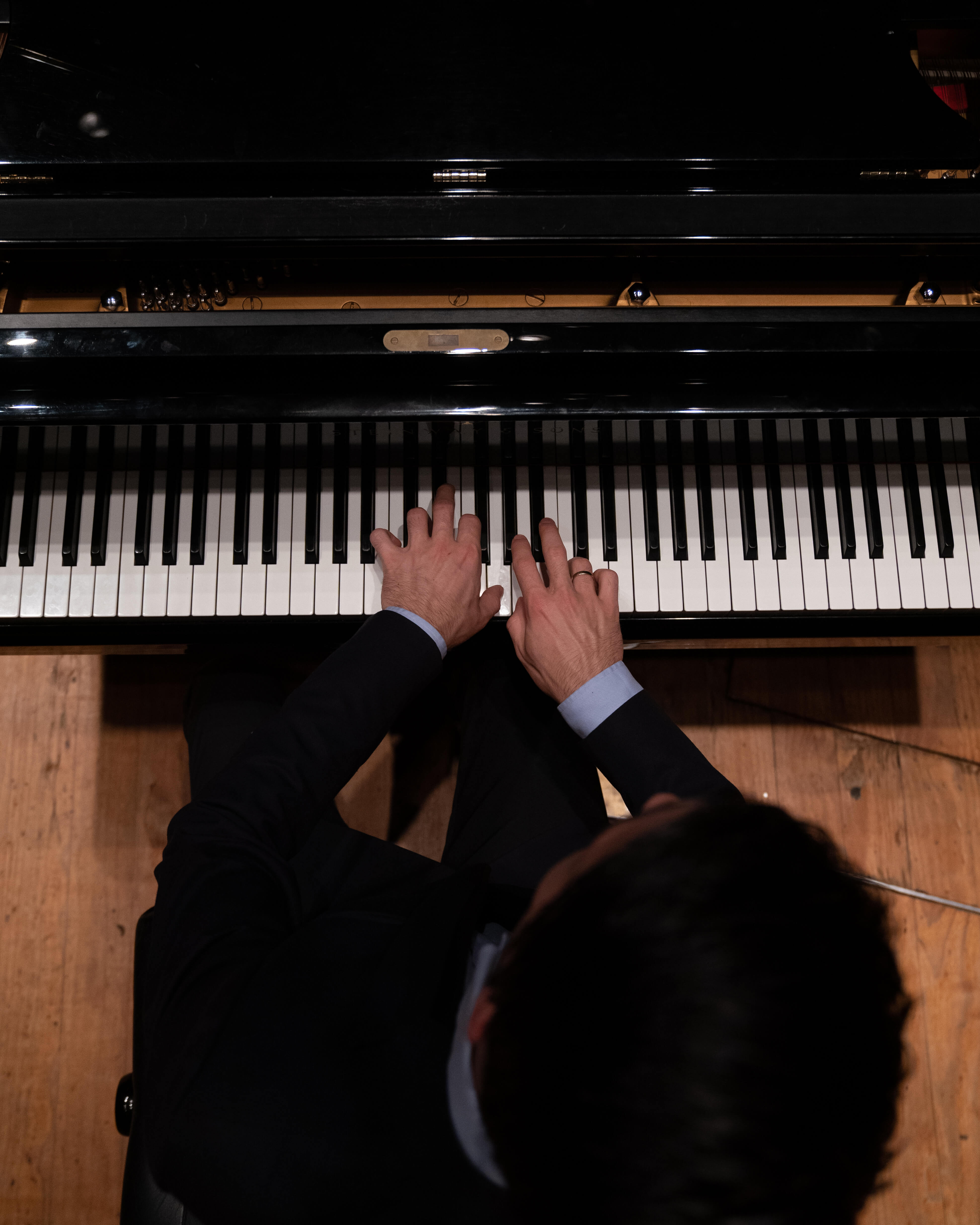 Pianist with their hands on the keys from above.