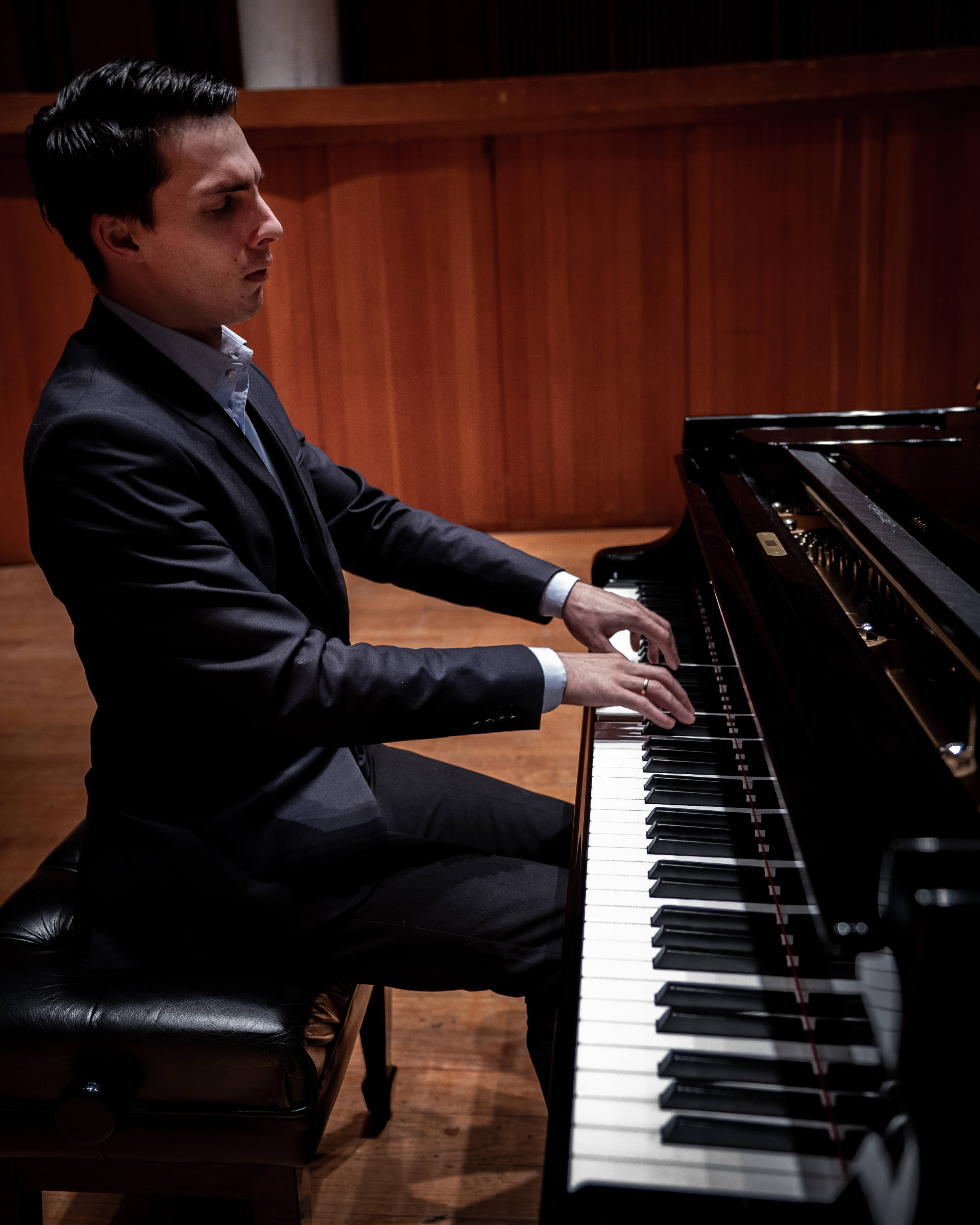 Pianist in a suit playing piano.