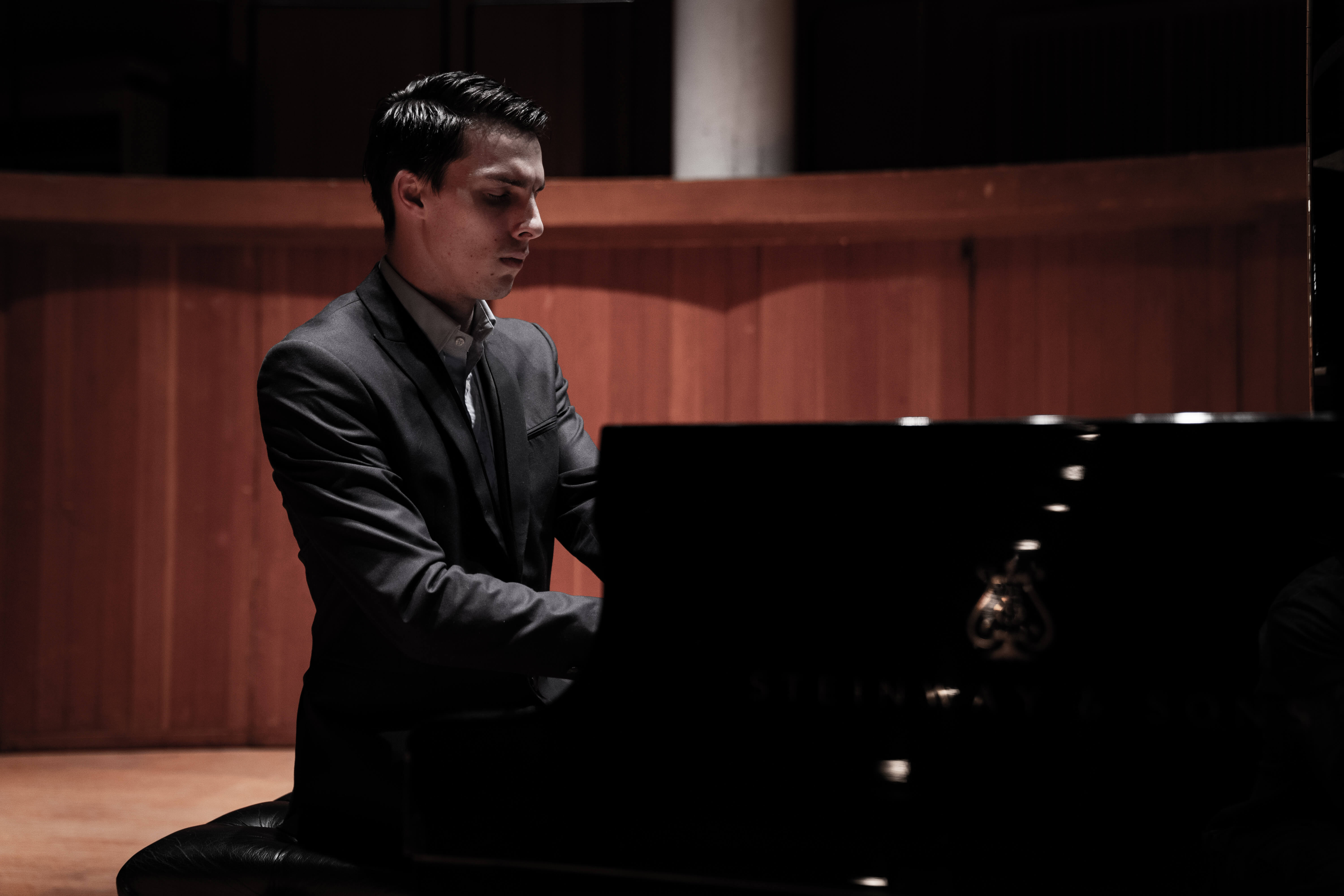 Pianist Liam Pitcher playing a grand piano in a wooden concert hall.
