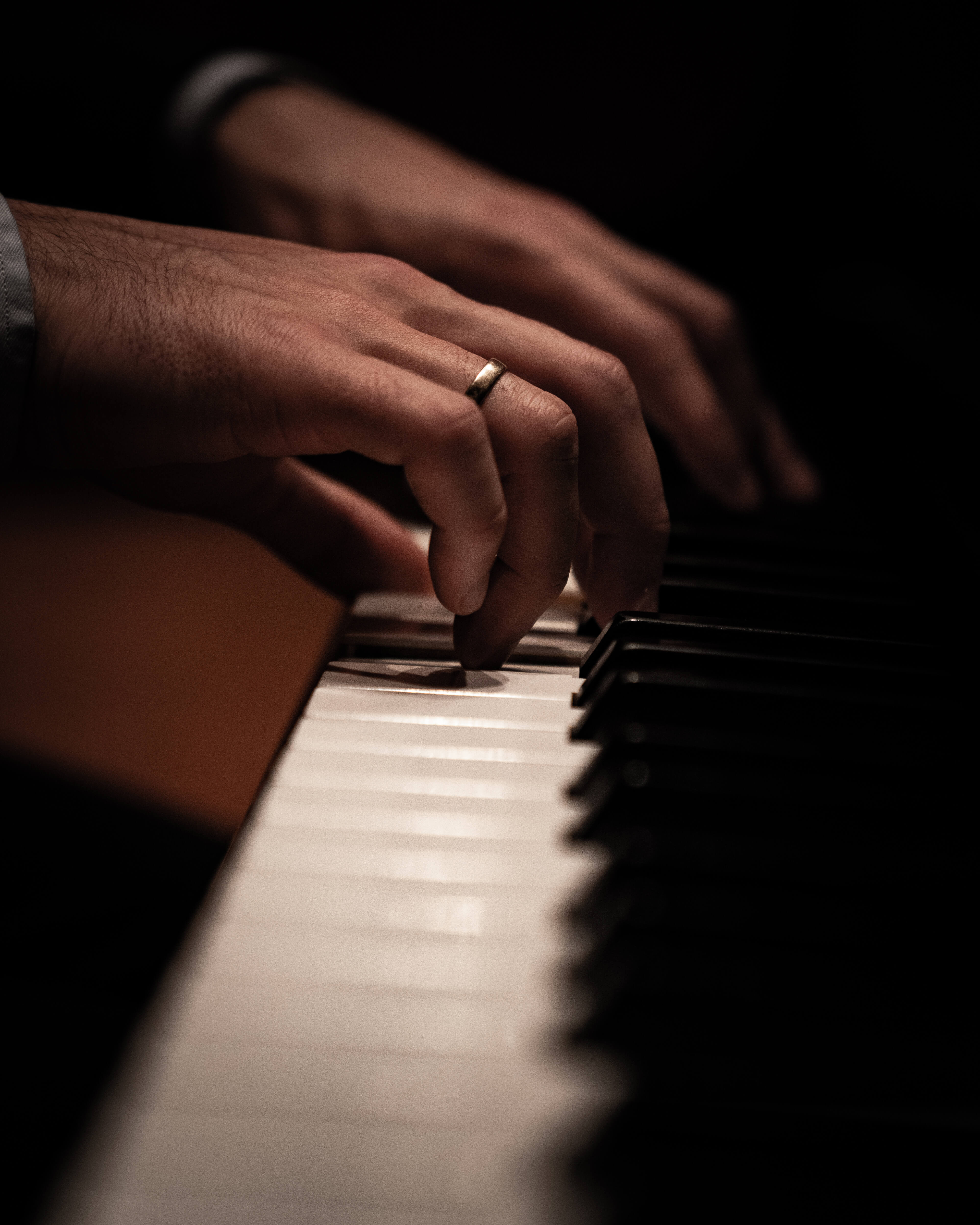 Two hands with a wedding ring playing piano.