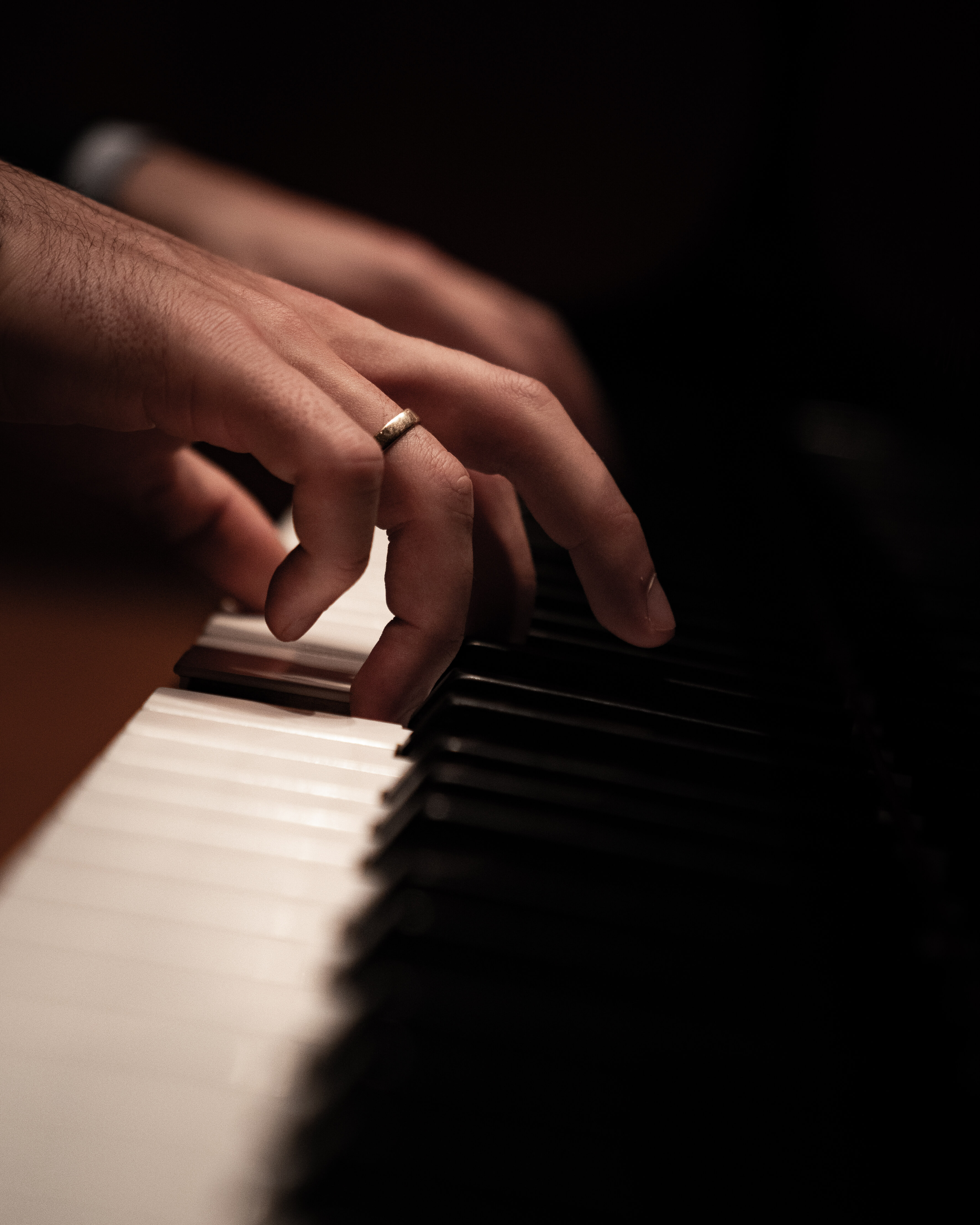 Hands on black and white piano keys.